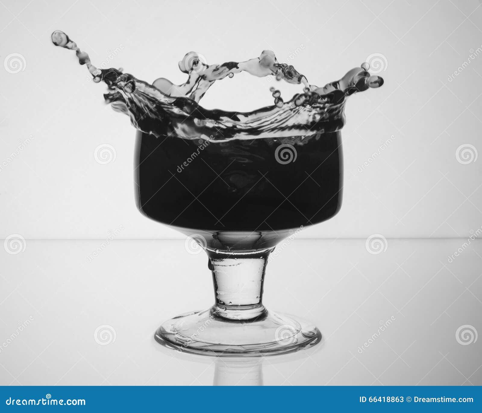 Exponeringsglas med en drink som ut plaskar
