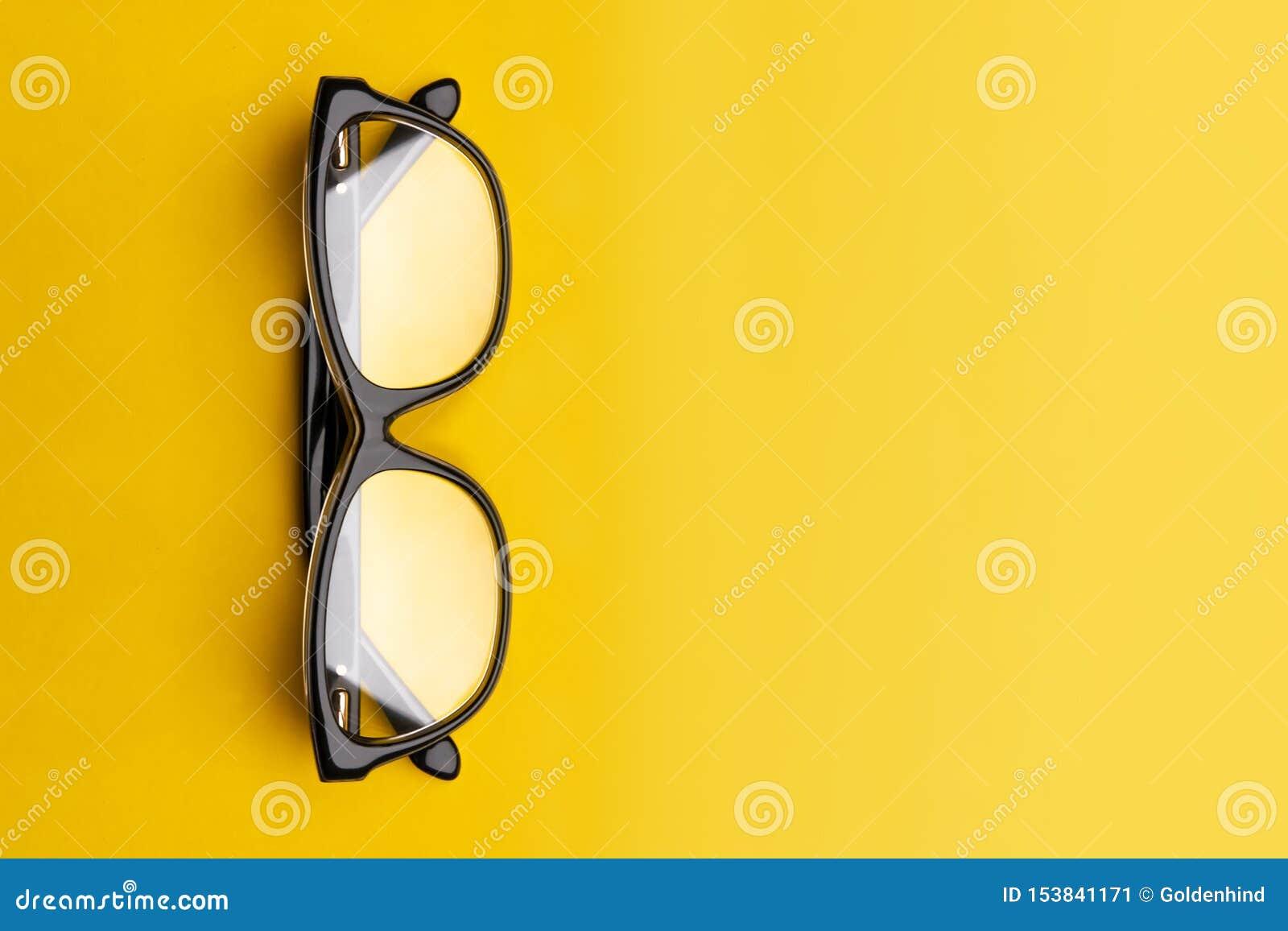 Exponeringsglas med genomskinliga linser som isoleras på gul bakgrund Fr?mre sikt med kopieringsutrymme
