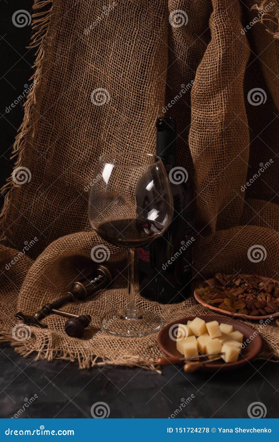Exponeringsglas och flaska av rött vin med ost, russin och muttrar på säckväv, mörk bakgrund
