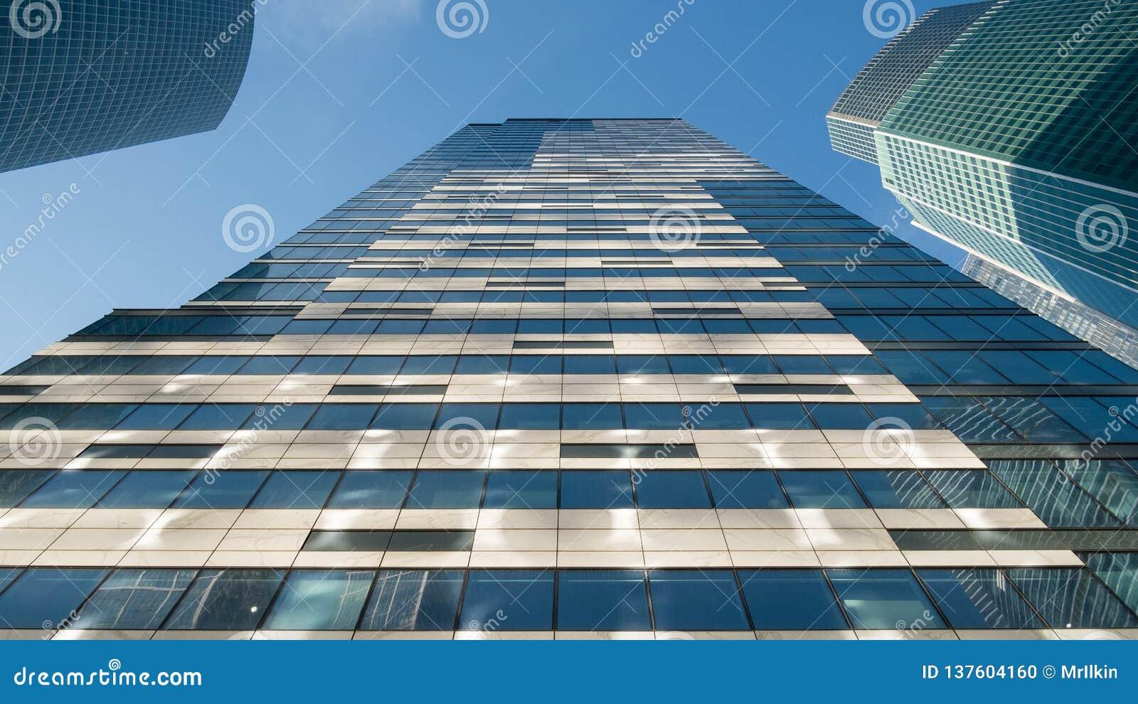 Exponeringsglasfönster av skyskrapor mot den blåa himlen