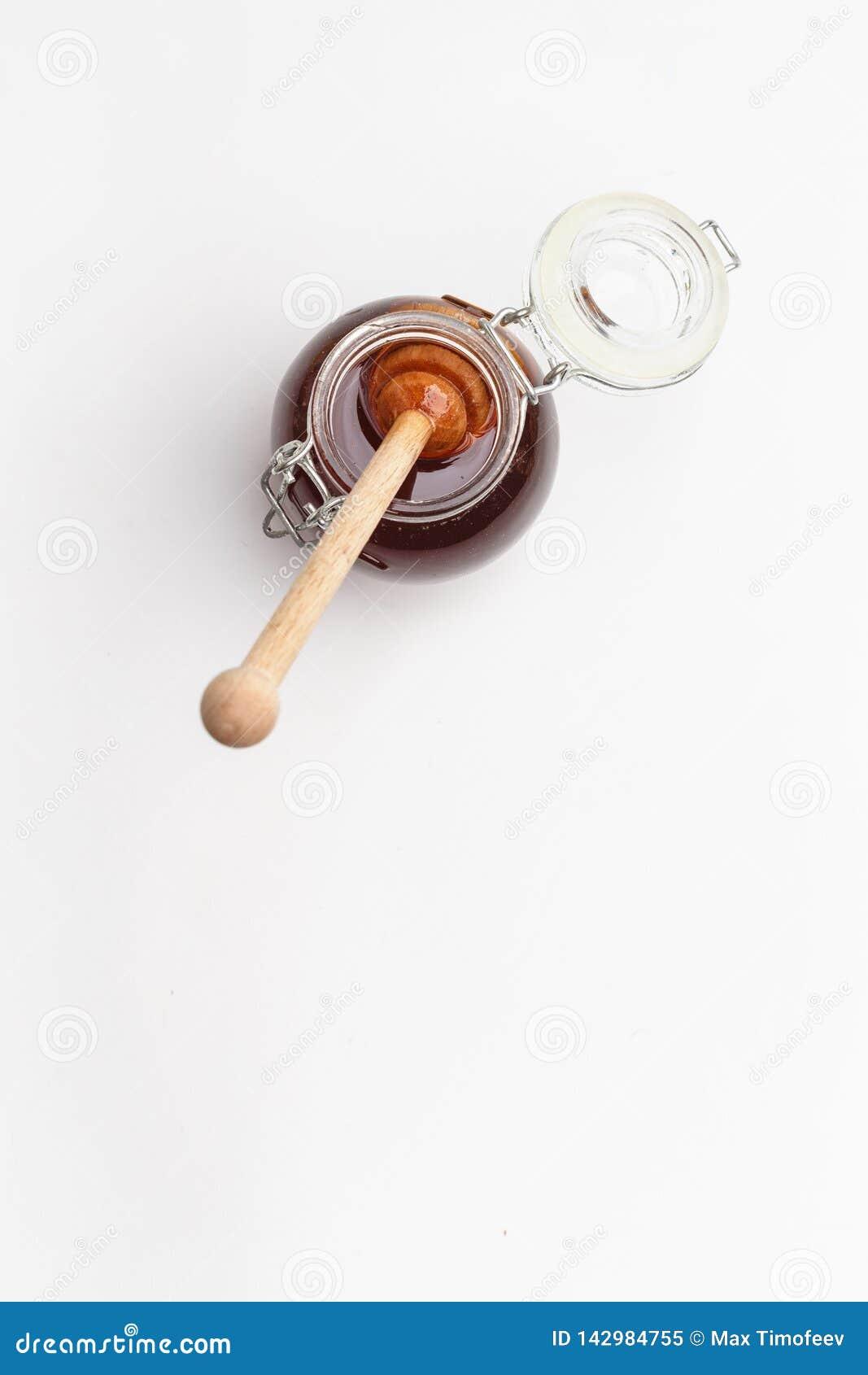 Exponeringsglaskrus med honung och träskeden på en vit bakgrund Top beskådar kopiera avstånd