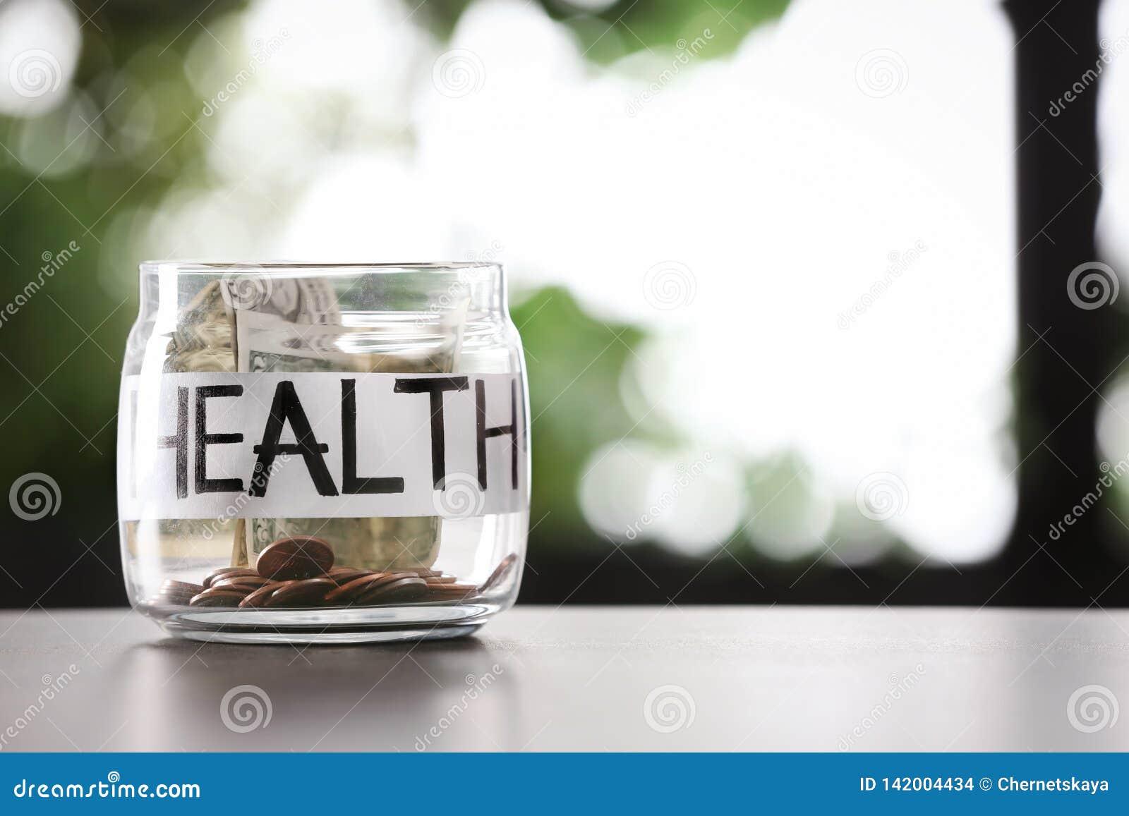 Exponeringsglaskrus med pengar och ord HÄLSA på tabellen mot suddig bakgrund