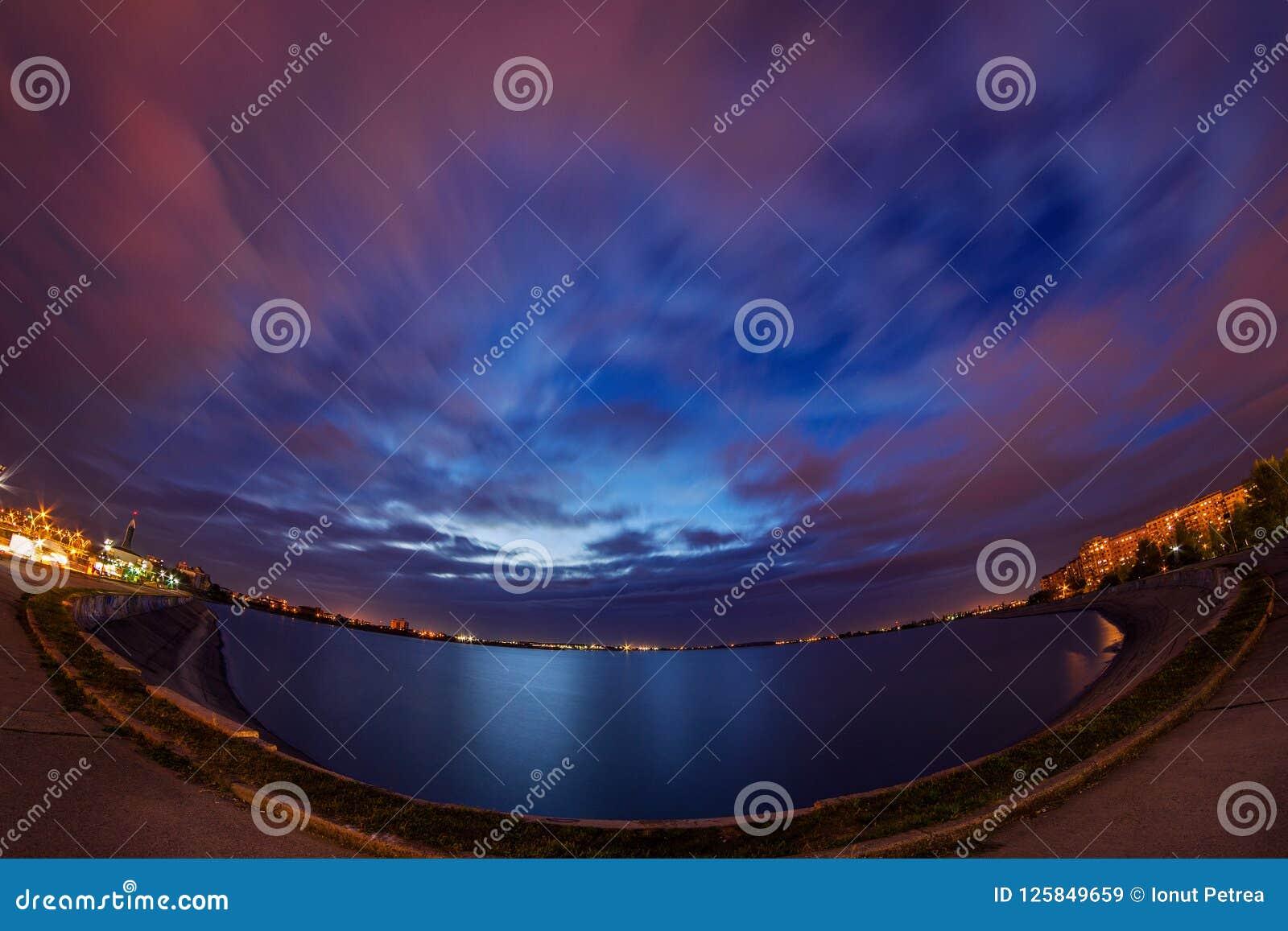 Exposição longa da cena urbana da noite com as nuvens no céu dramático e