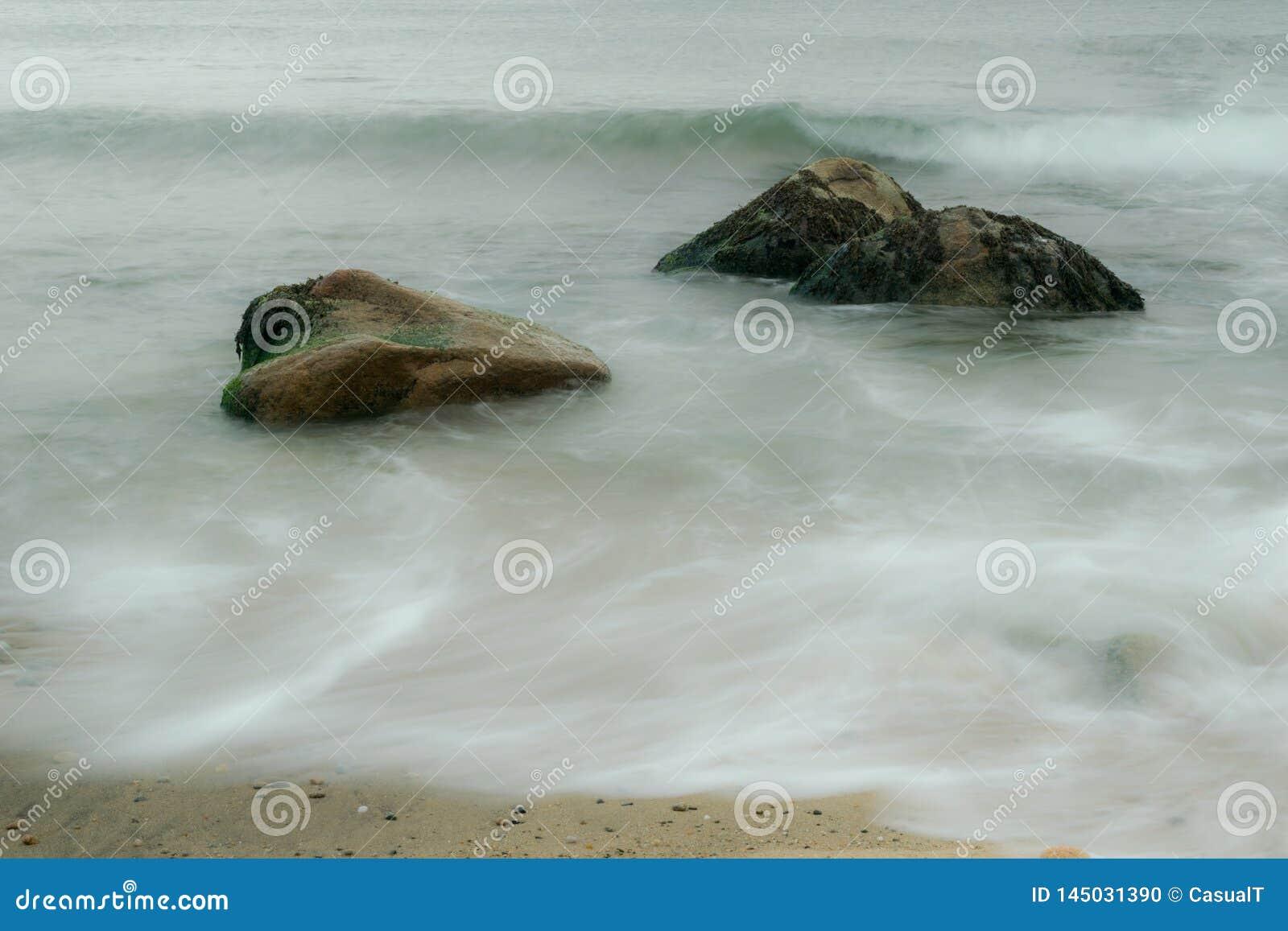 Exposição longa de ondas de oceano, fluindo em torno dos pedregulhos cobertos alga, ilha de bloco, RI