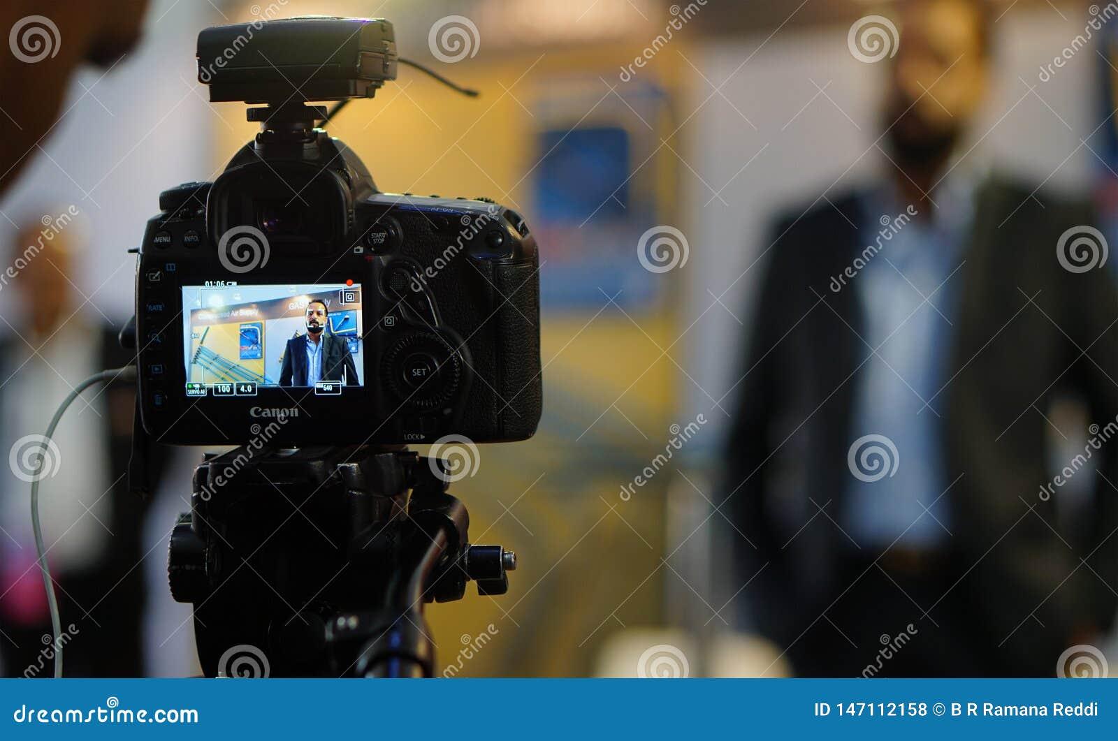 Exposi??o ou monitor da entrevista video do tiro da c?mera de DSLR em uma feira profissional