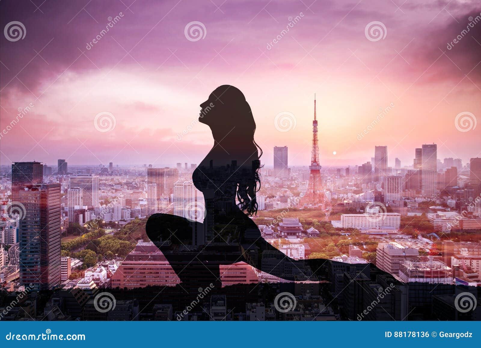 Exposición doble de la mujer de la yoga de la silueta contra la ciudad de Tokio