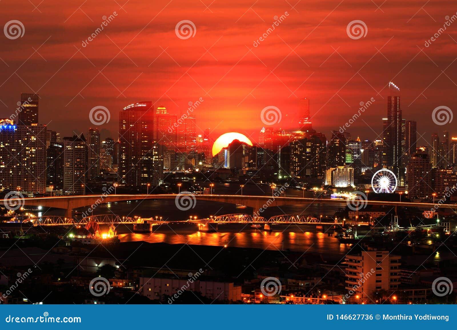 Exposición doble sobre de la ciudad de la escena de la noche en el fondo hermoso de la puesta del sol, mundo del concepto calient