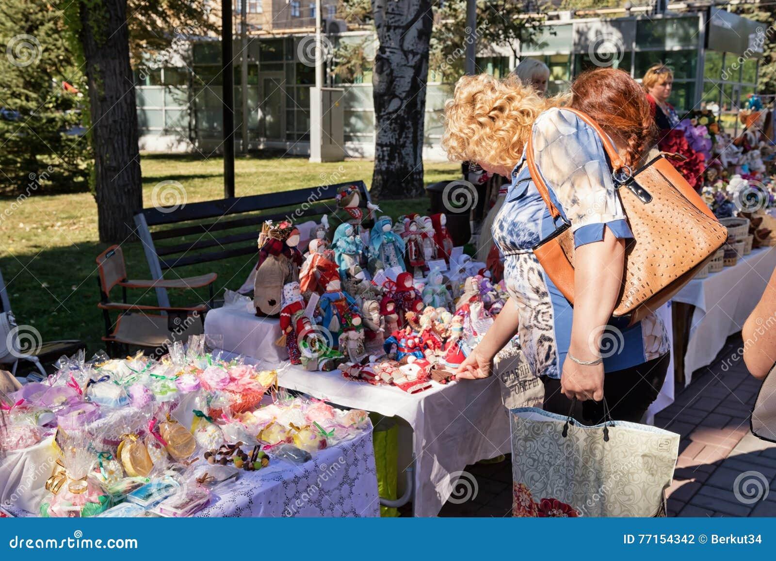 Exposition-vente des poupées et des souvenirs faits main sur les rues d