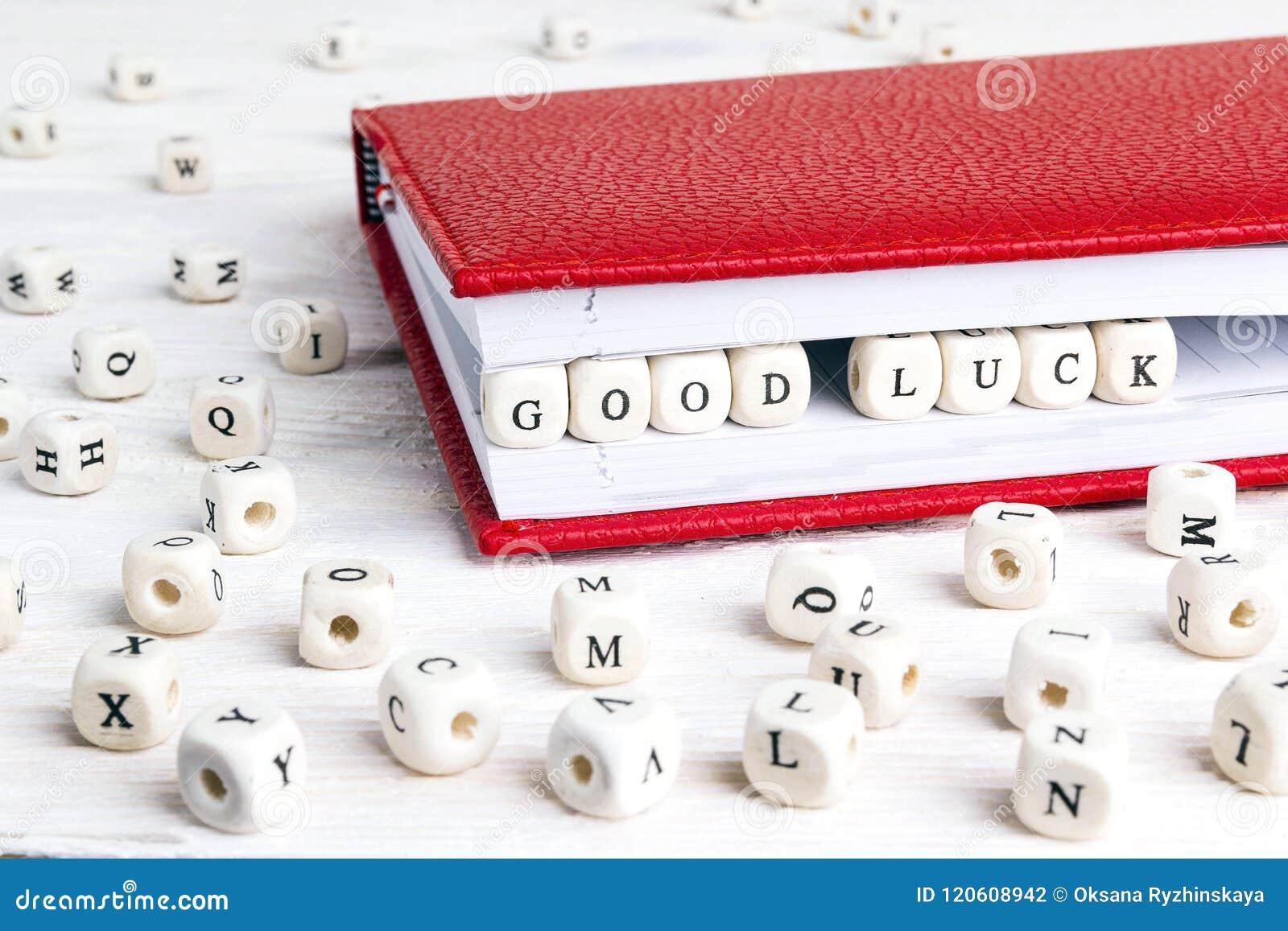 Exprese la suerte de Cood escrita en bloques de madera en cuaderno rojo en whi