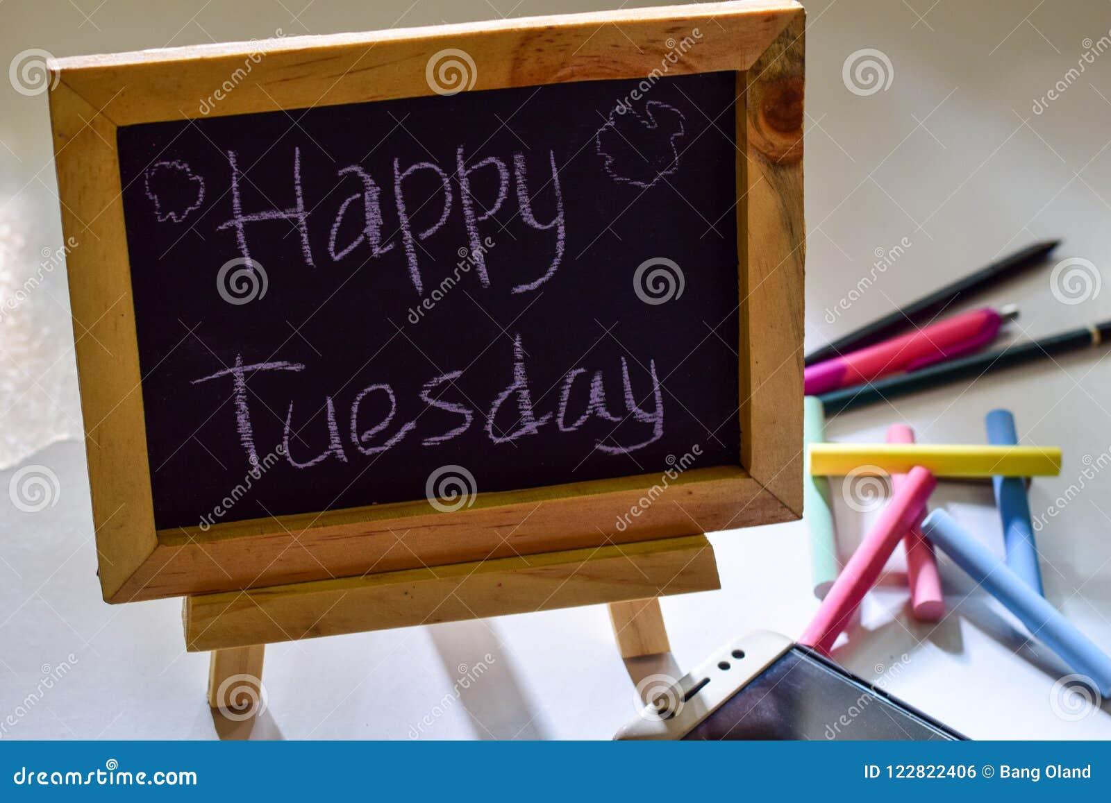 Exprese martes feliz escrito en una pizarra en ella y el smartphone, tiza colorida