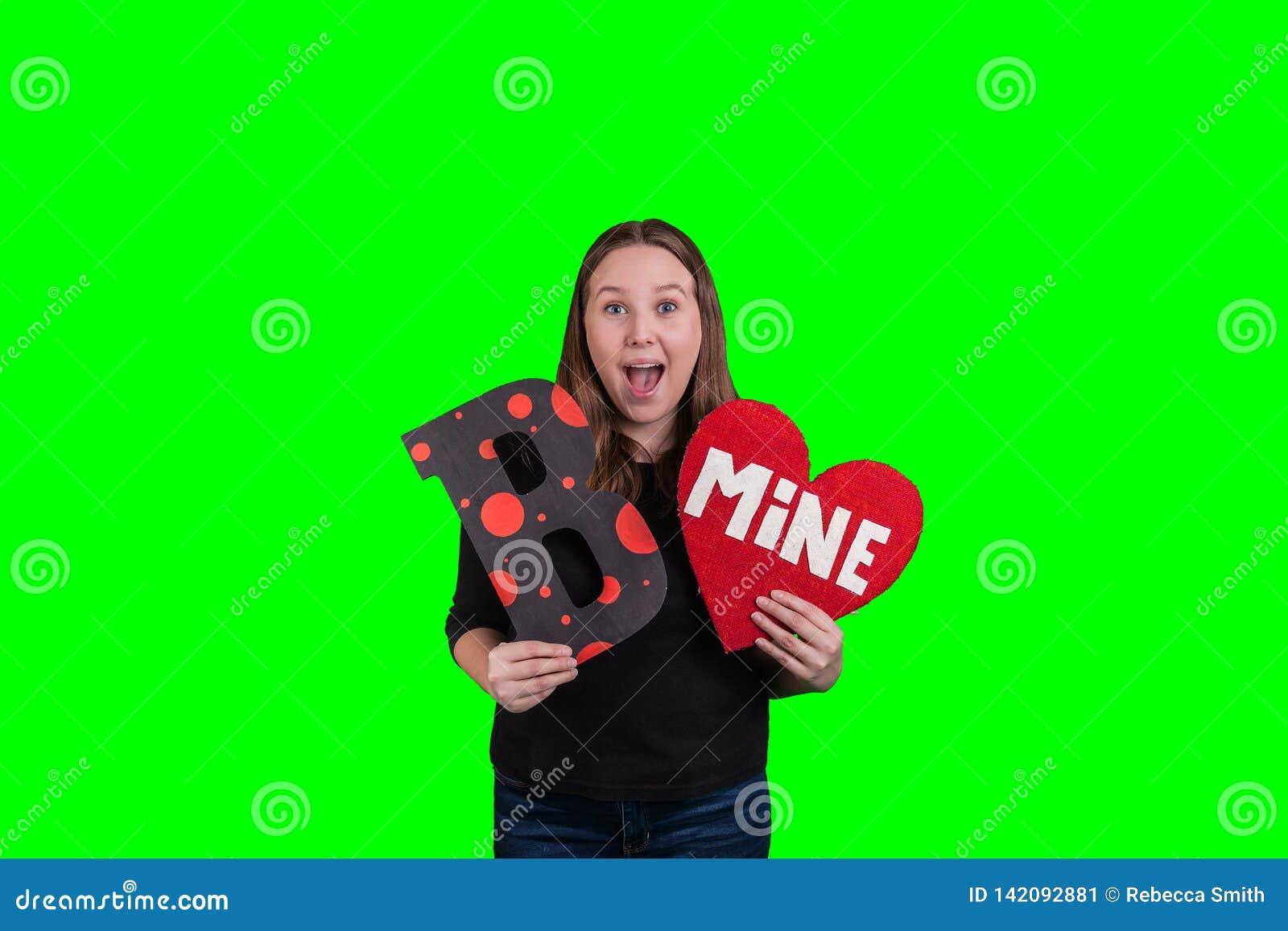 Expresión facial emocionada en la cara de las hembras que lleva a cabo una letra B y una muestra en forma de corazón de la MINA