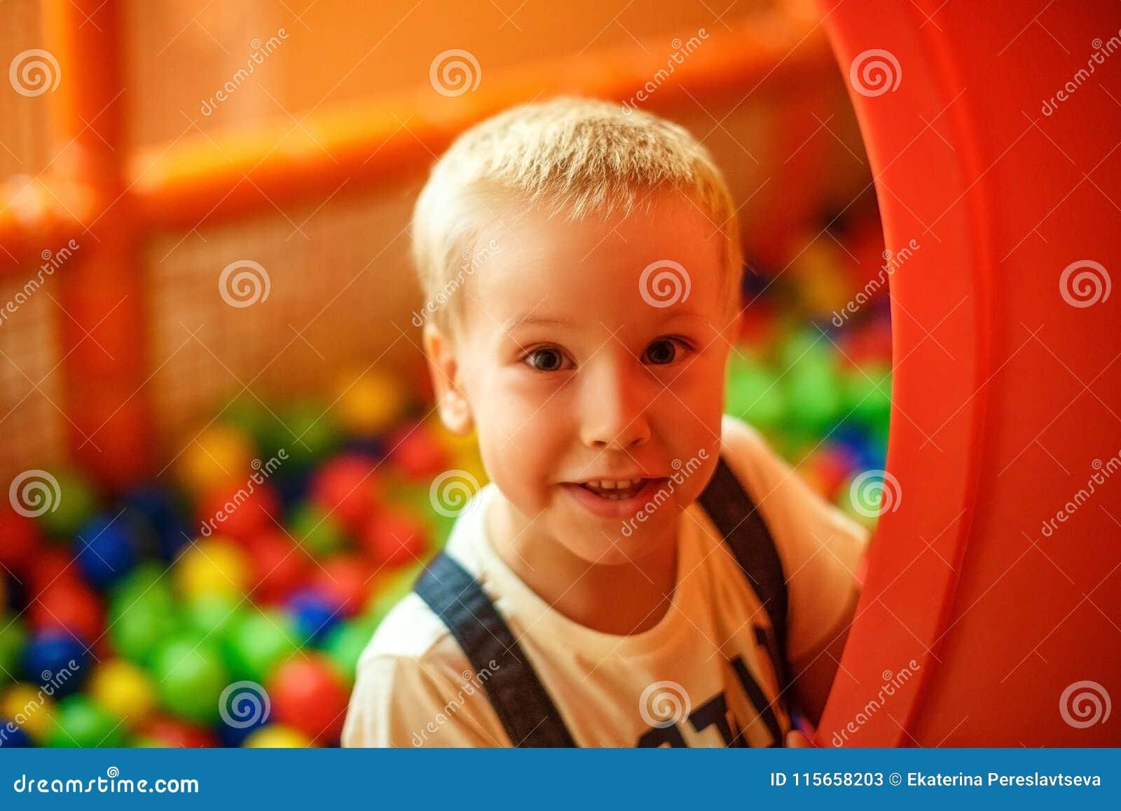 Expresión feliz de la cara del ` s del niño, jugando en el cuarto del ` s de los niños