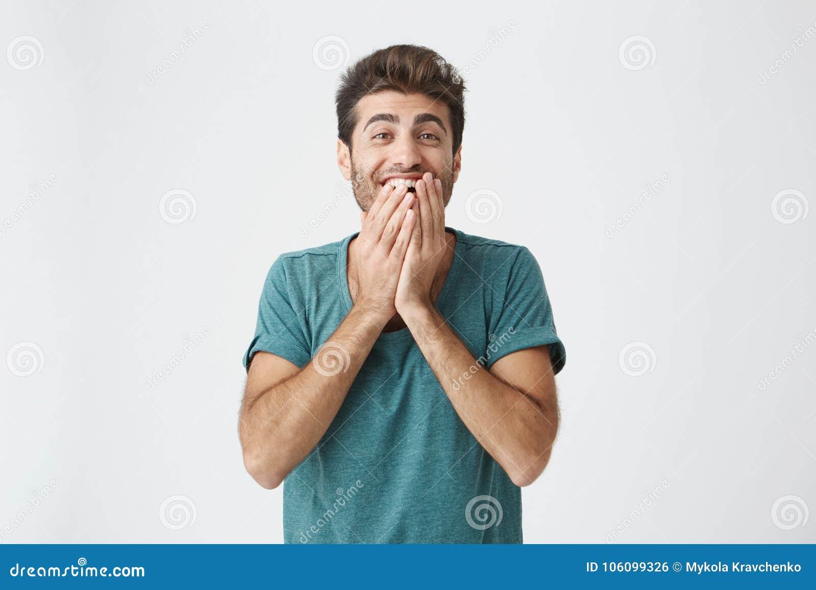 Expresiones, emociones y sensaciones del rostro humano Hombre joven barbudo asombroso y sorprendido en camiseta azul que señala e