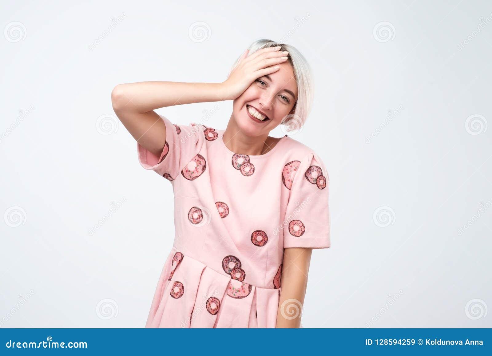 Expresiones y emociones del rostro humano Mujer hermosa joven alegre positiva en vestido rosado que se ríe de broma