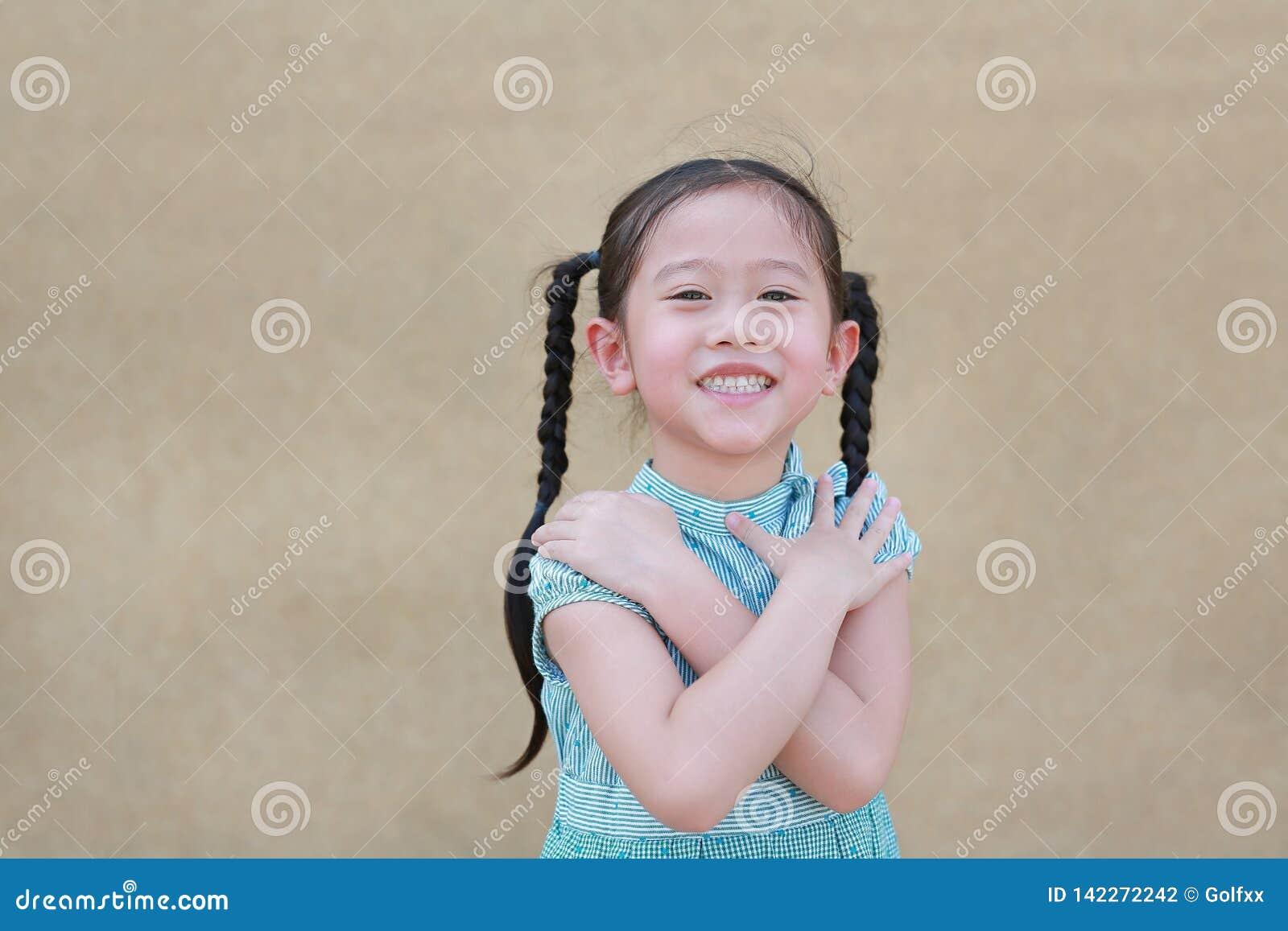 Expressão asiática pequena feliz da menina da criança para cruzar seus braço e sorriso Conceito seguro e alegre
