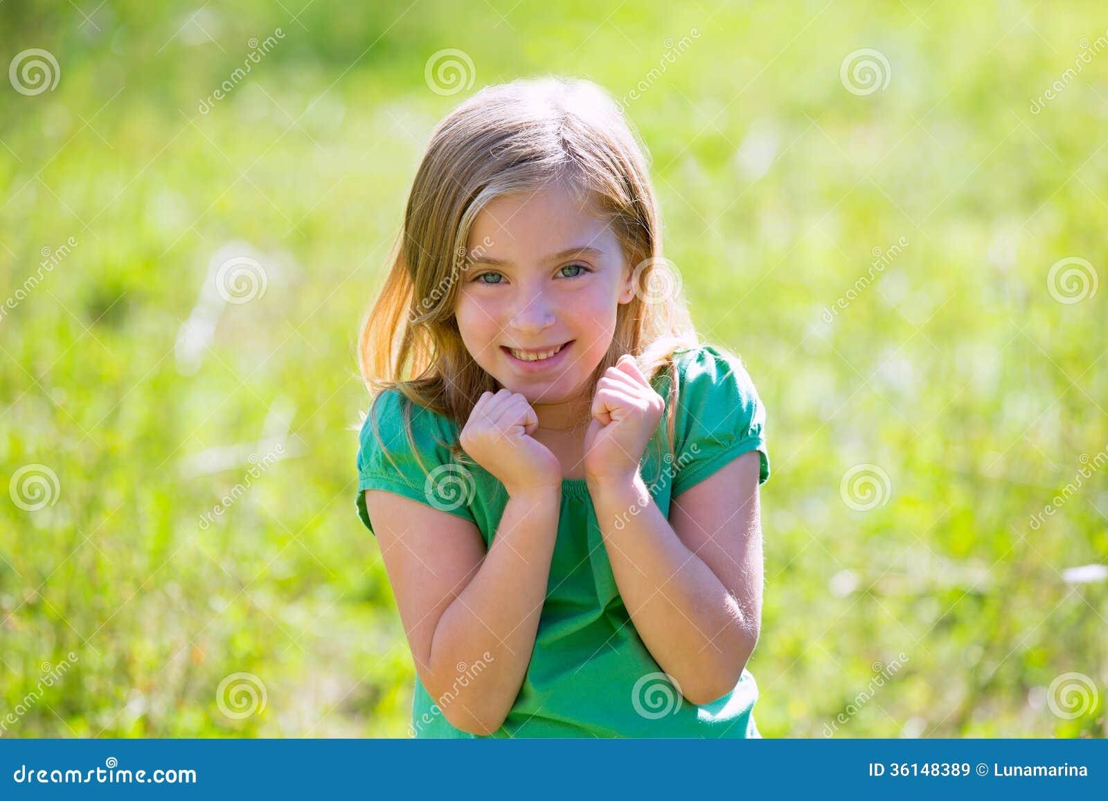 Expressão entusiasmado do gesto da menina loura da criança em exterior verde