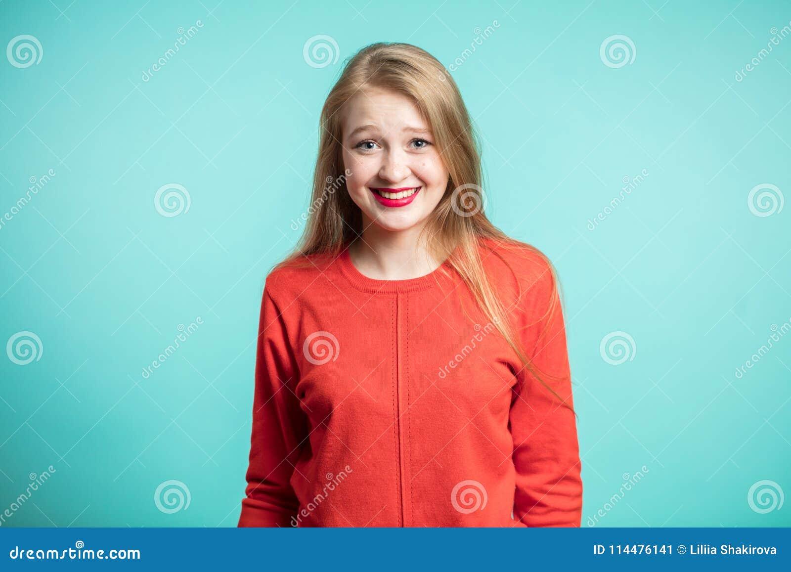 Expressões e emoções do rosto humano Jovem mulher alegre feliz que veste seu júbilo vermelho do vestido na notícia positiva, olha