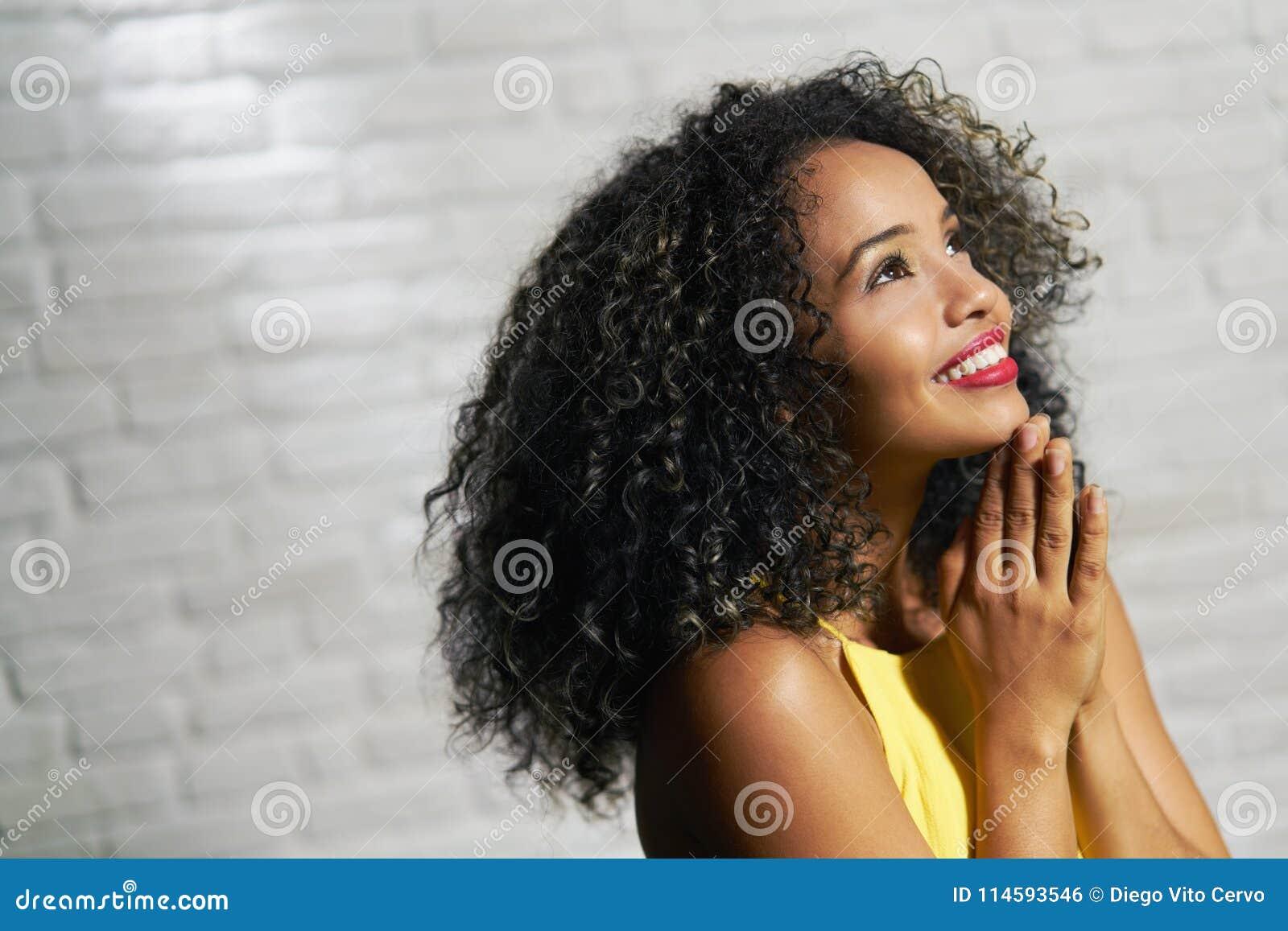 Expressões faciais da mulher negra nova na parede de tijolo