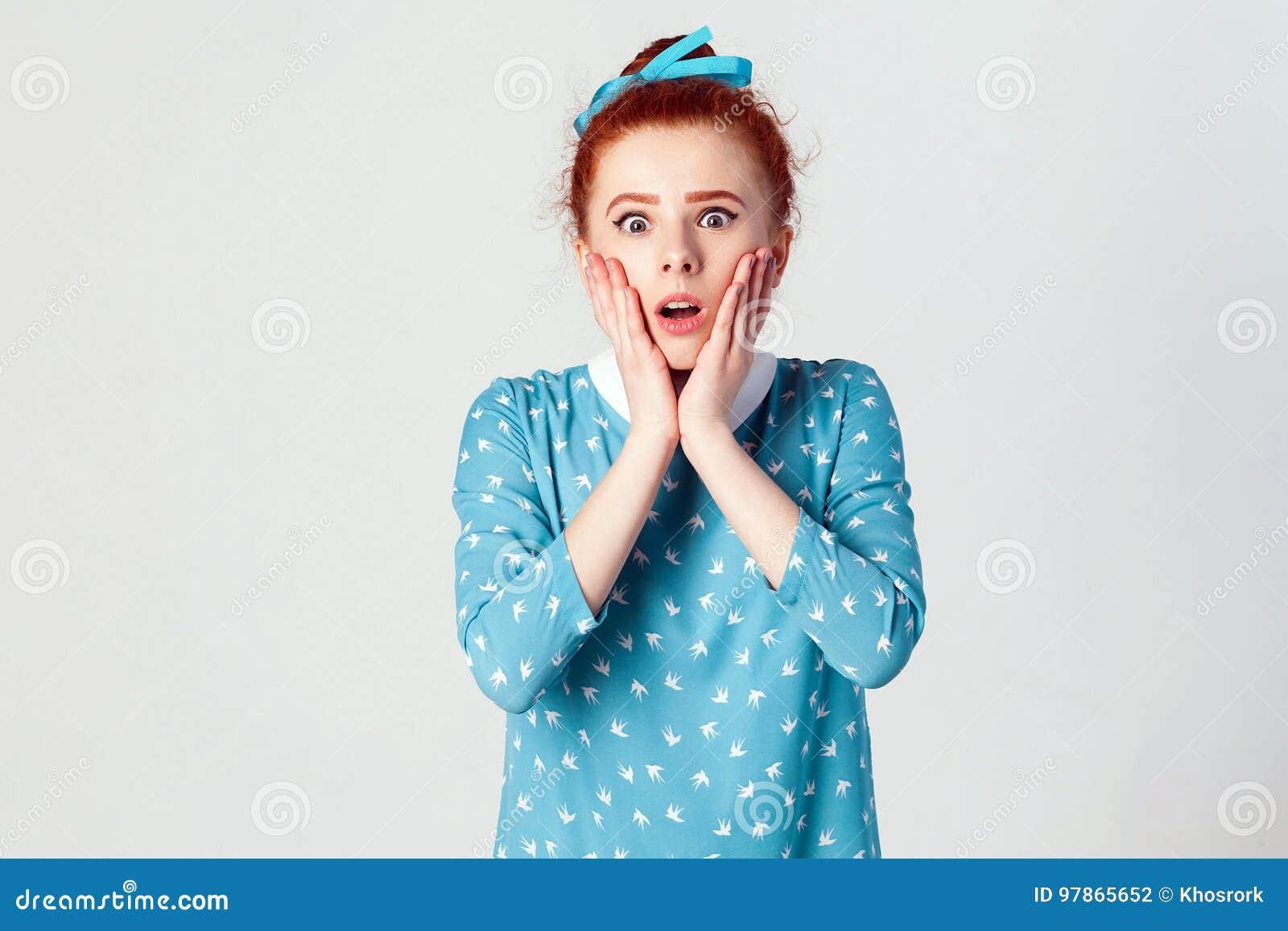 Expressions et émotions de visage humain Jeune fille rousse criant avec le choc, tenant des mains sur ses joues