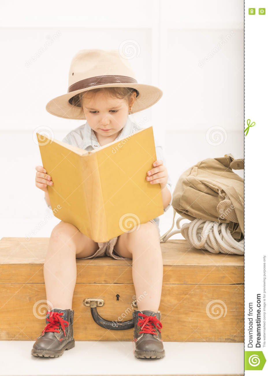 da05f7839cc0d An adorable little girl in a safari hat and explorer clothes reading old  book sitting on a wooden suitcase with backpack and safety rope