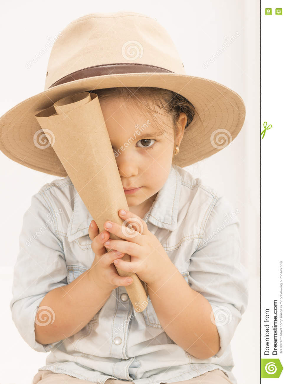 858589fcaeb40 Adorable little girl in a safari hat and explorer clothes hiding her face  behind treasure map