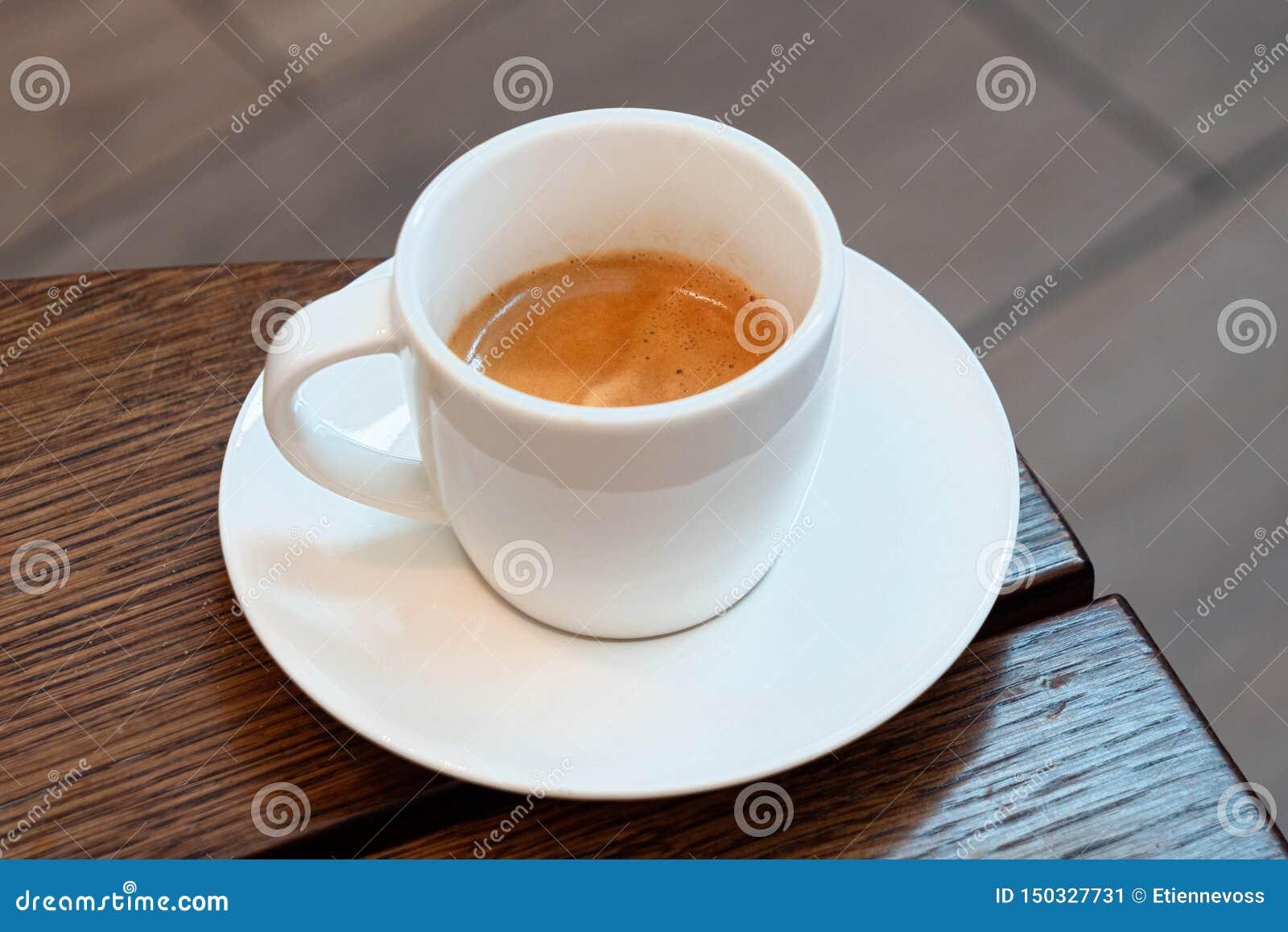 Expresso italien dans une tasse en céramique blanche avec la soucoupe sur une table en bois brune Fond de Brurred