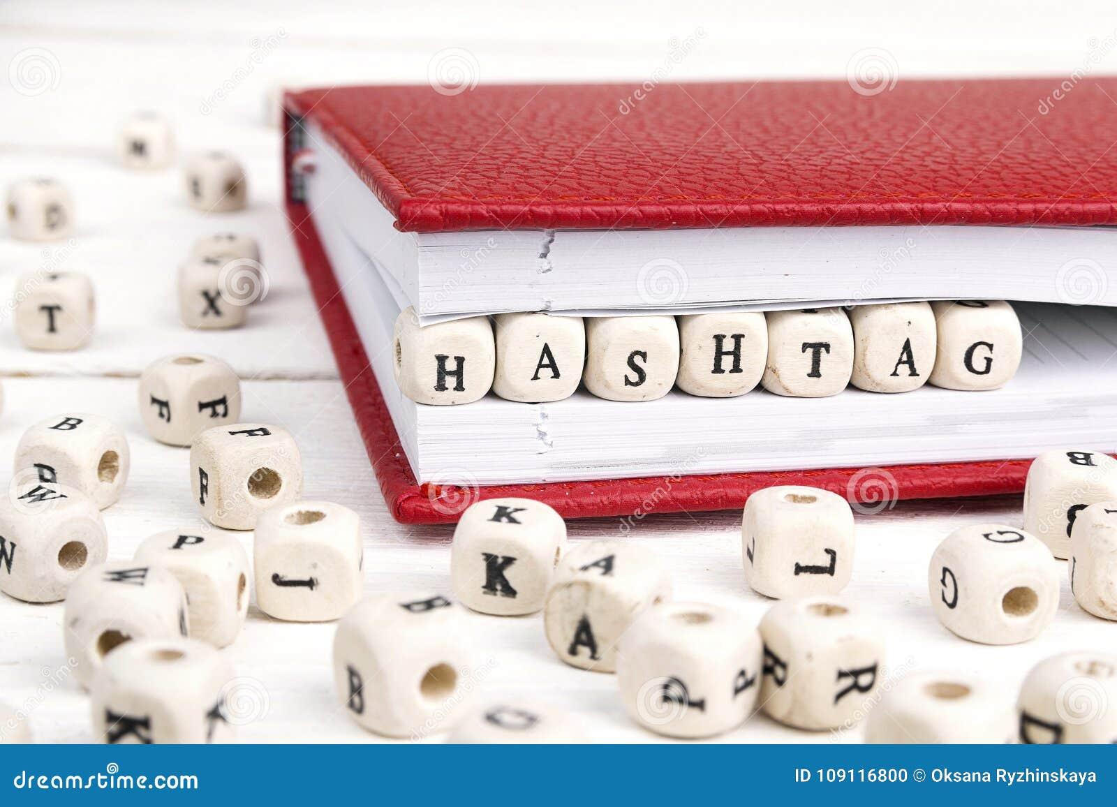 Exprima Hashtag escrito em blocos de madeira no caderno vermelho na tabela de madeira branca