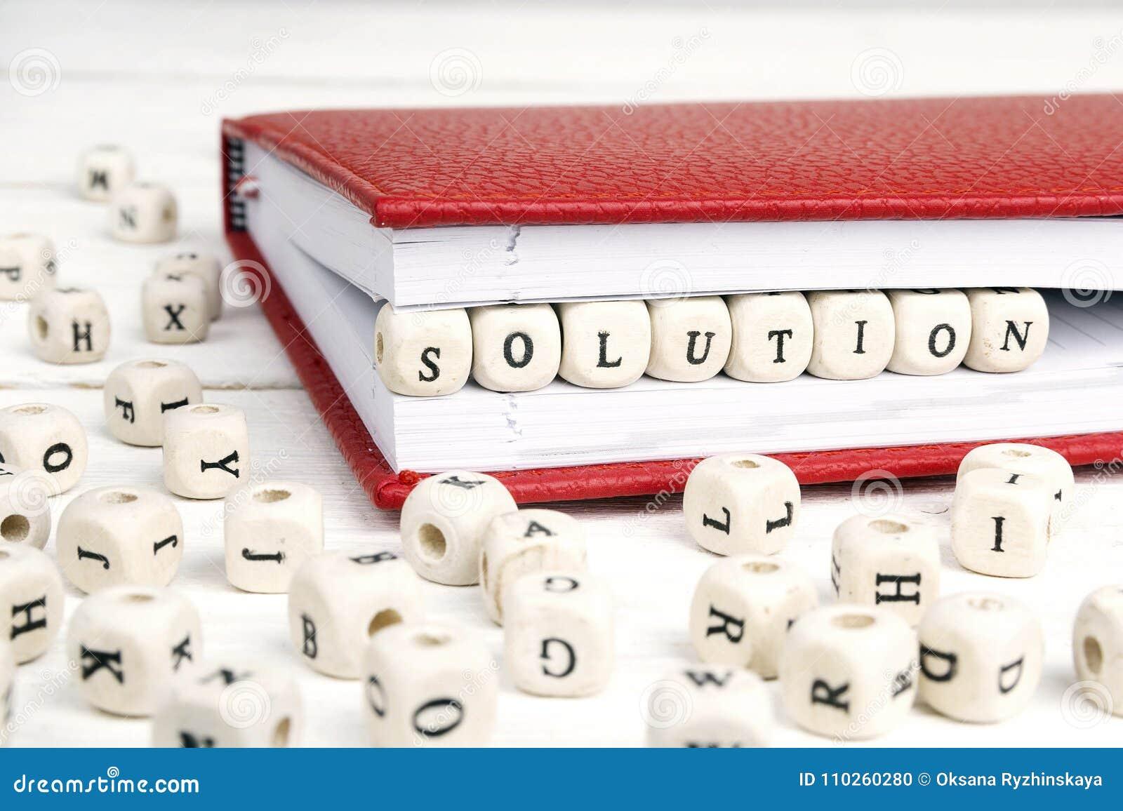 Exprima a solução escrita em blocos de madeira no caderno vermelho no branco