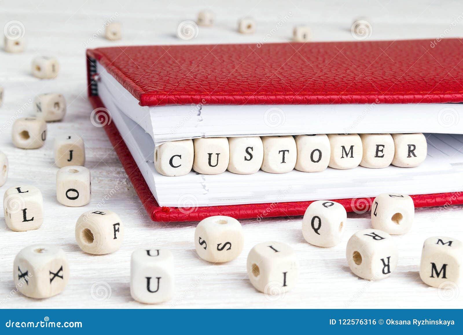 Exprimez le client écrit dans les blocs en bois dans le carnet rouge sur le blanc