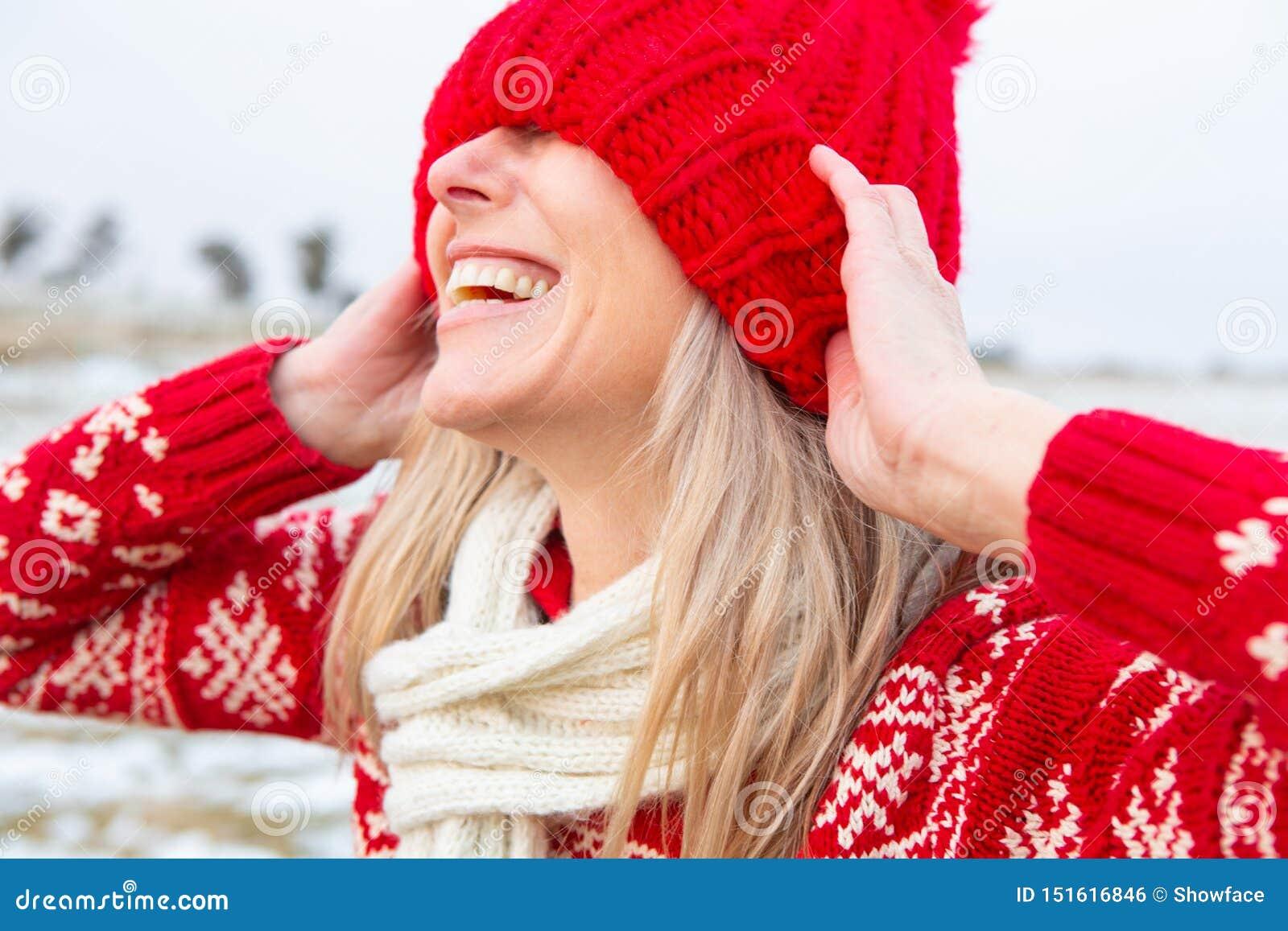 Extérieur heureux de femme tirant la calotte au-dessus des yeux