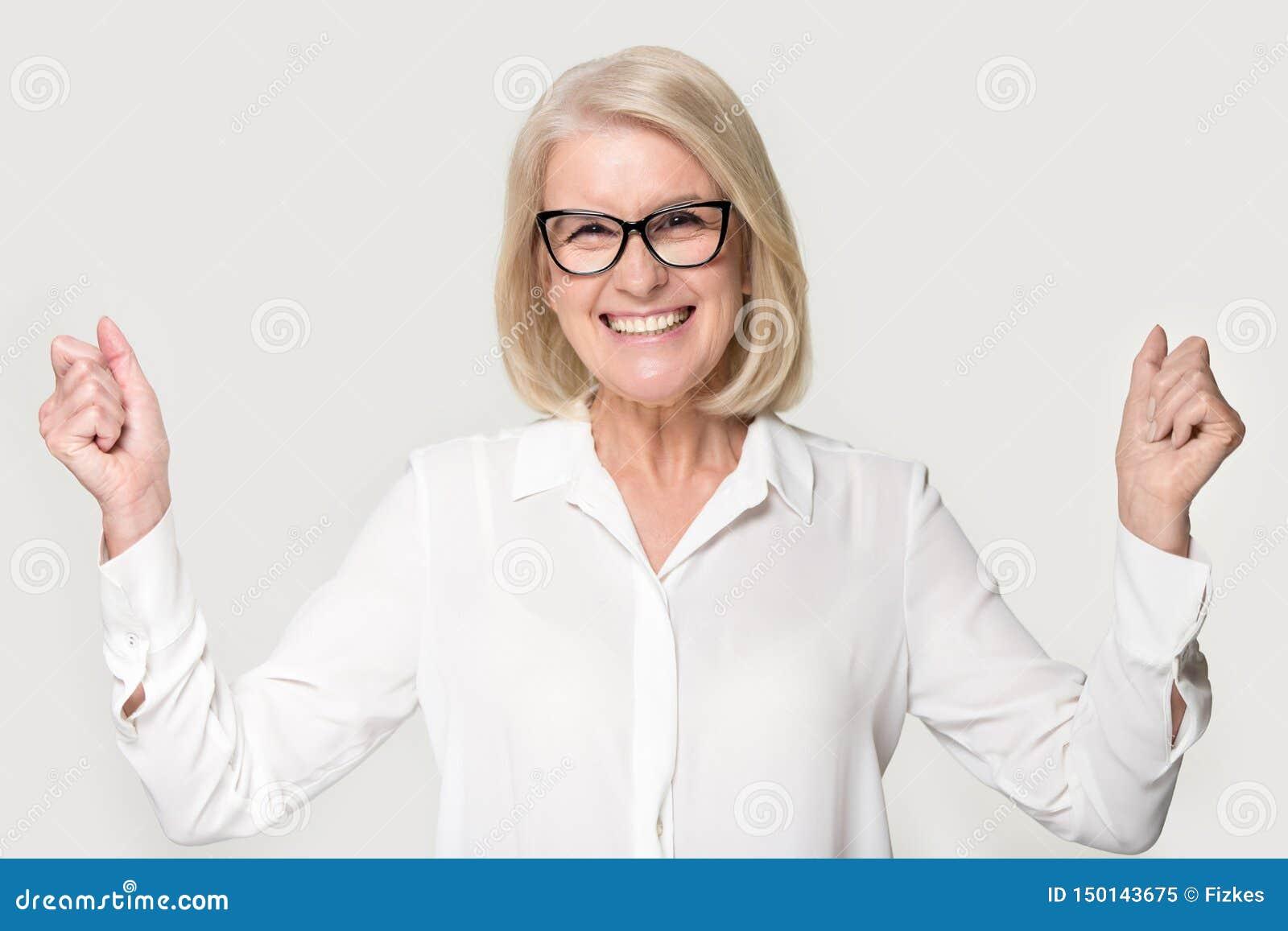 Extatisk hög kvinna som firar framgång som poserar på grå studiobakgrund