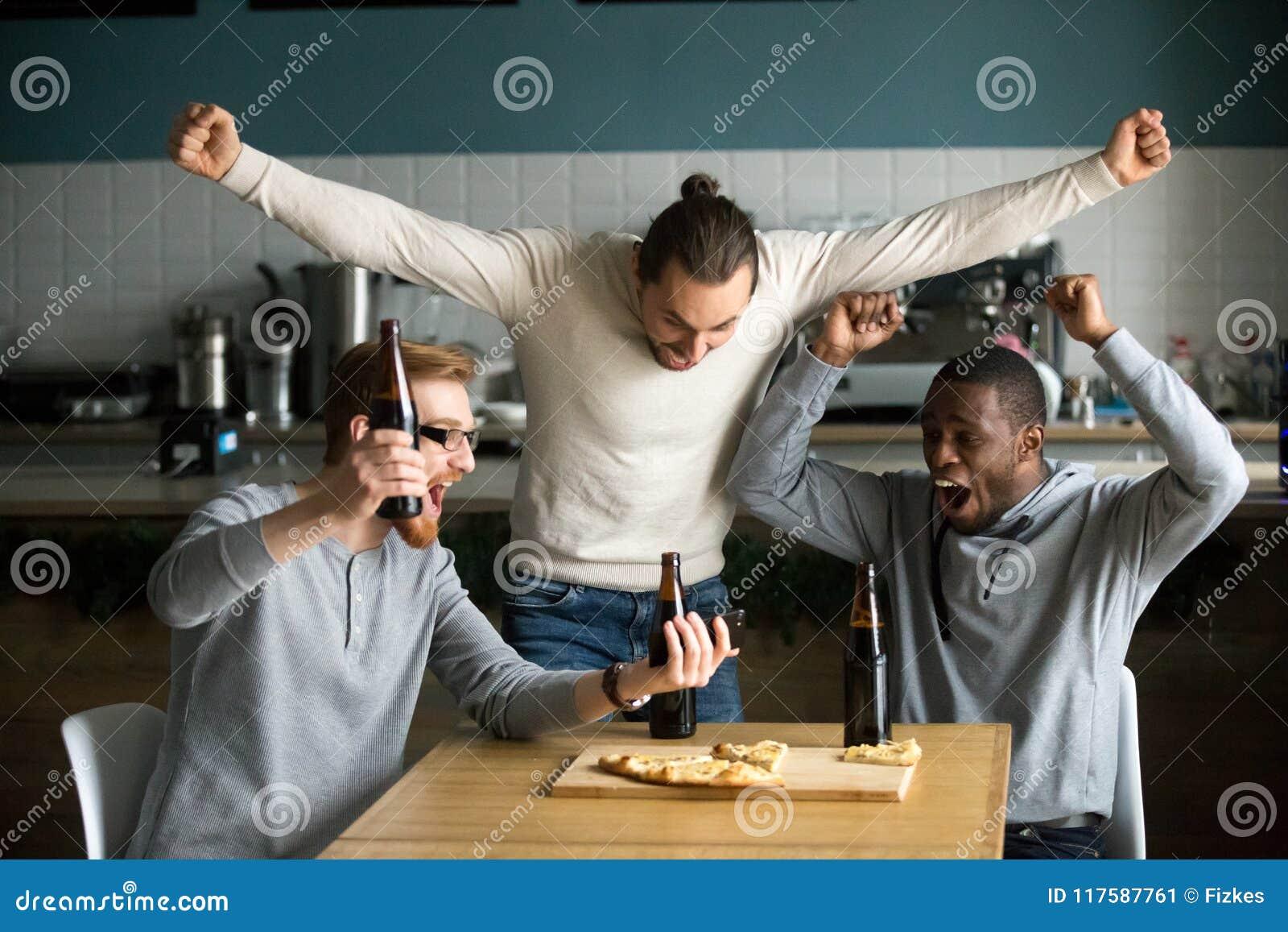 Extatiska män som firar den hållande ögonen på leken för seger på smartphonen, sp