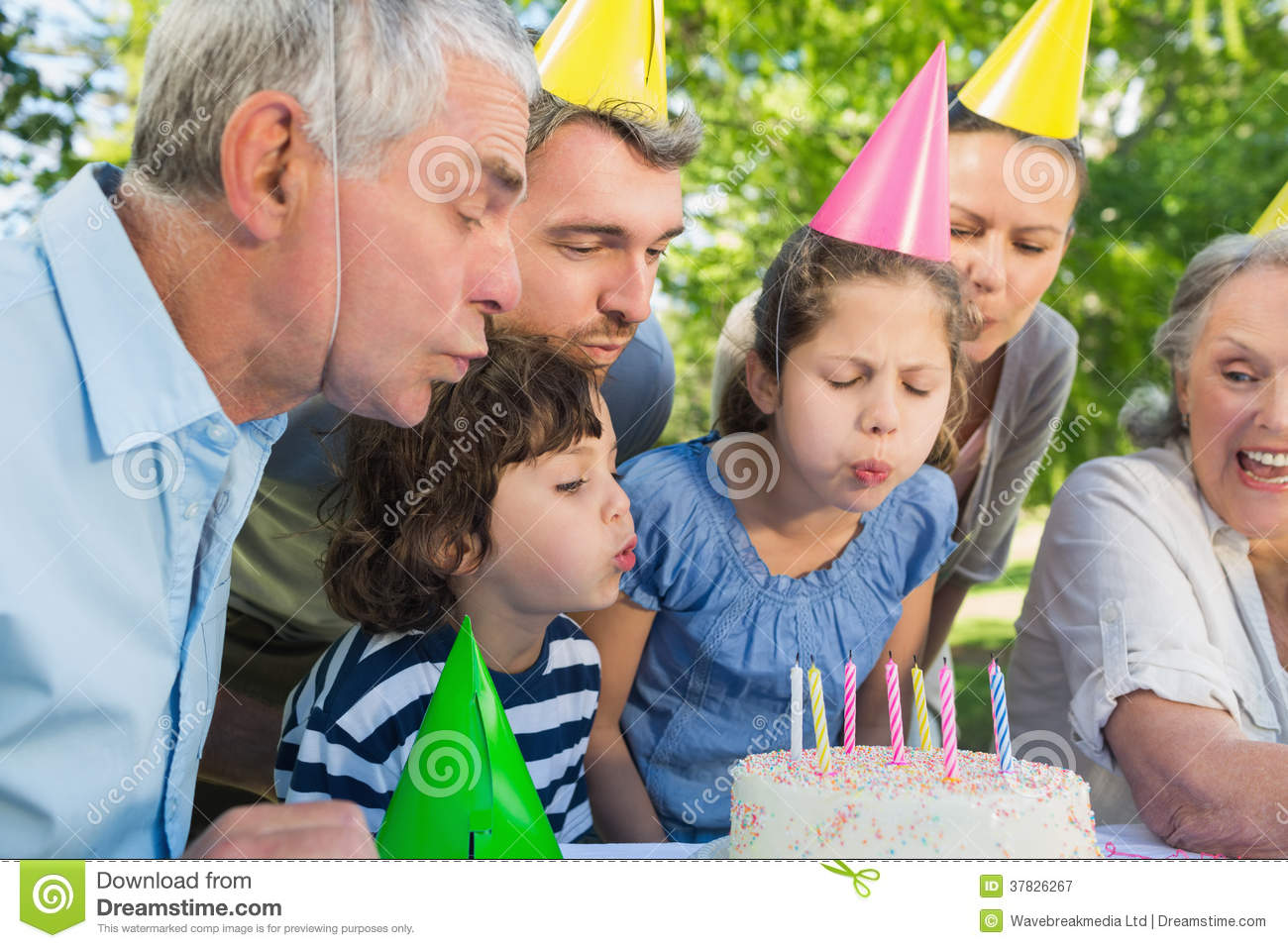 Extended Family In Party Hats Blowing Birthday Cake Stock