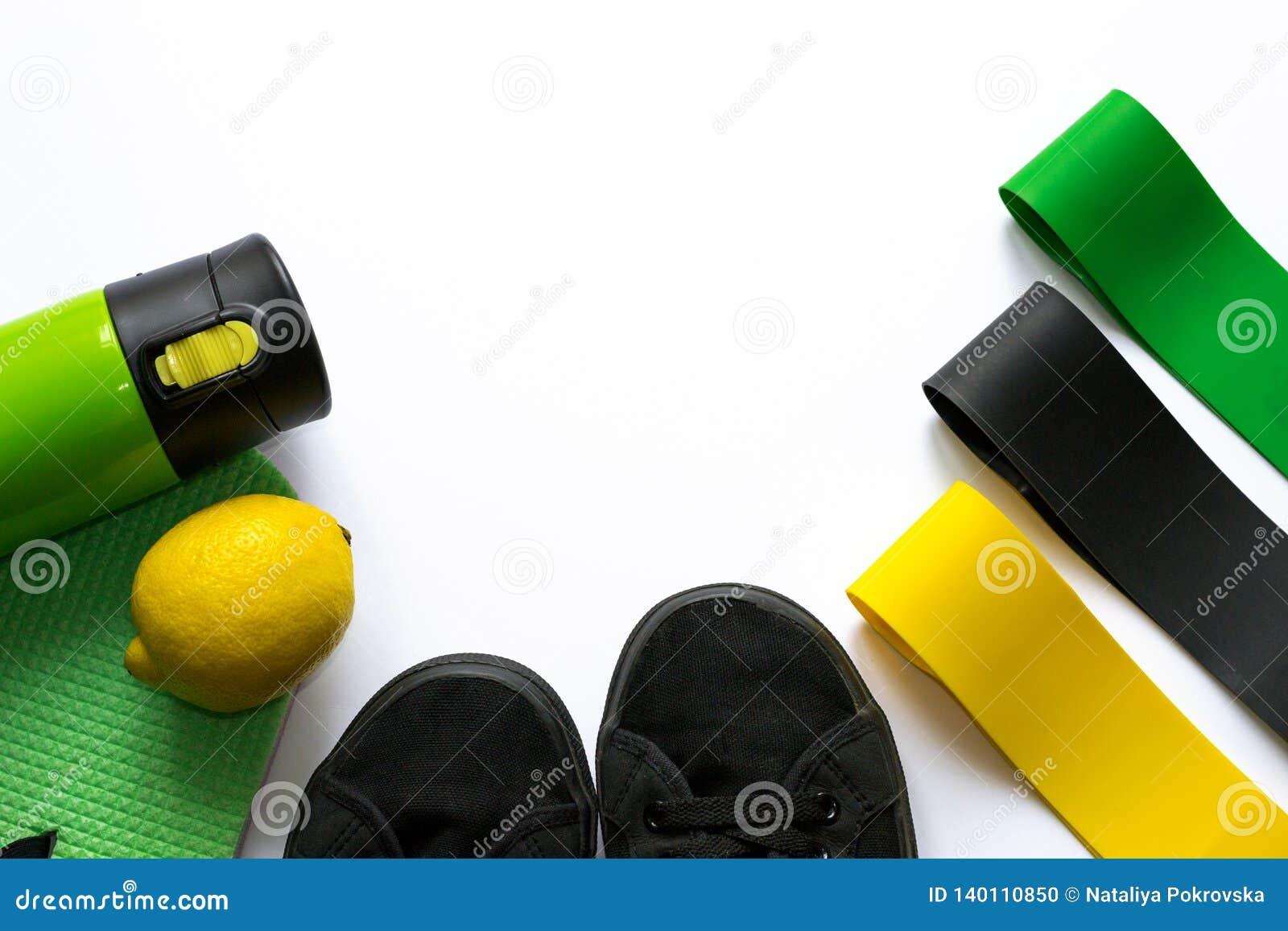 Extenseurs élastiques de gomme de forme physique de couleurs jaunes, vertes et noires sur le fond blanc avec le copyspace Bouteil
