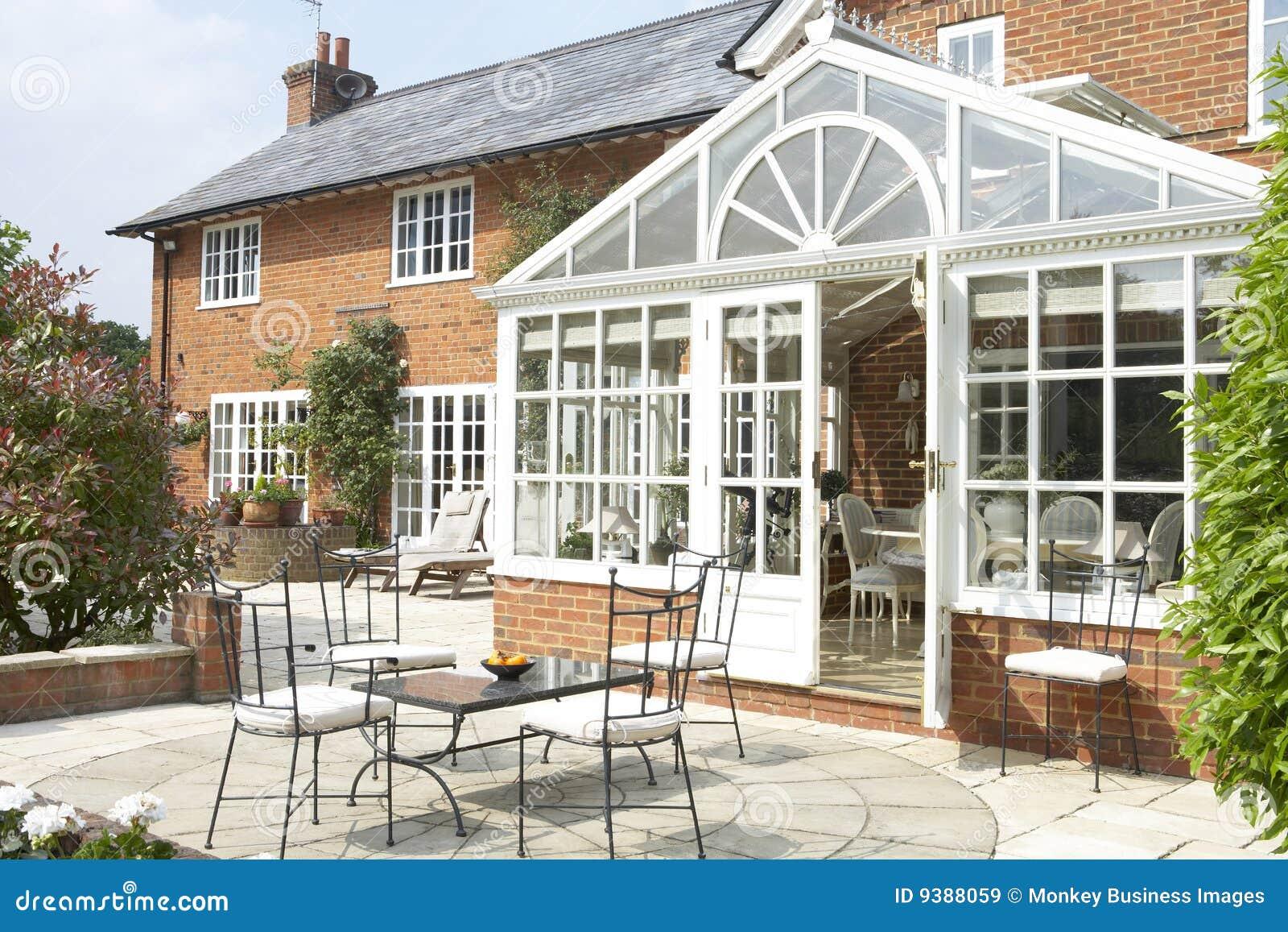 Exterior de la casa con el invernadero y el patio
