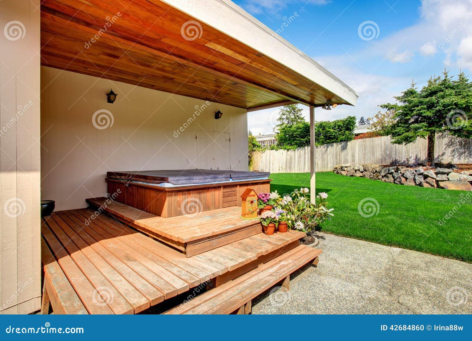 Exterior de la casa cubierta del patio trasero con el for Construir jacuzzi exterior