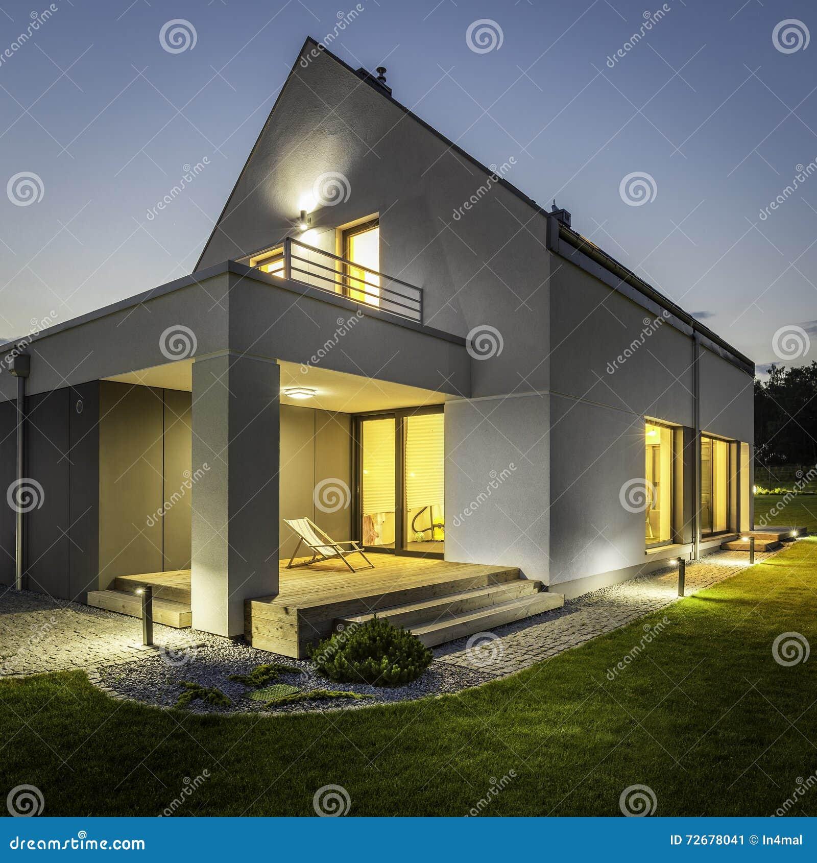 Exterior de la casa iluminada entre verde