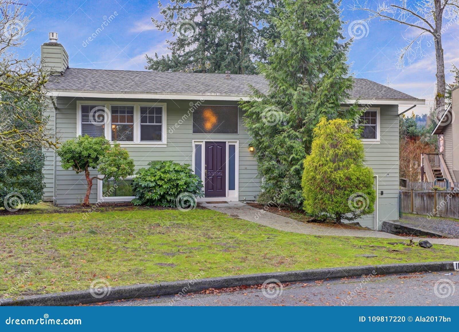 Exterior do renovado agradavelmente em casa com tapume verde e guarnição branca
