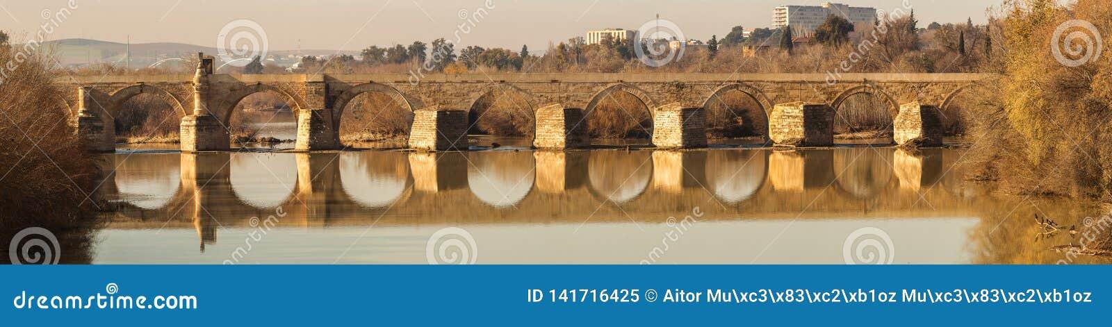 Old stone Roman bridge across Guadalquivir river in sunlight in Cordoba, Spain