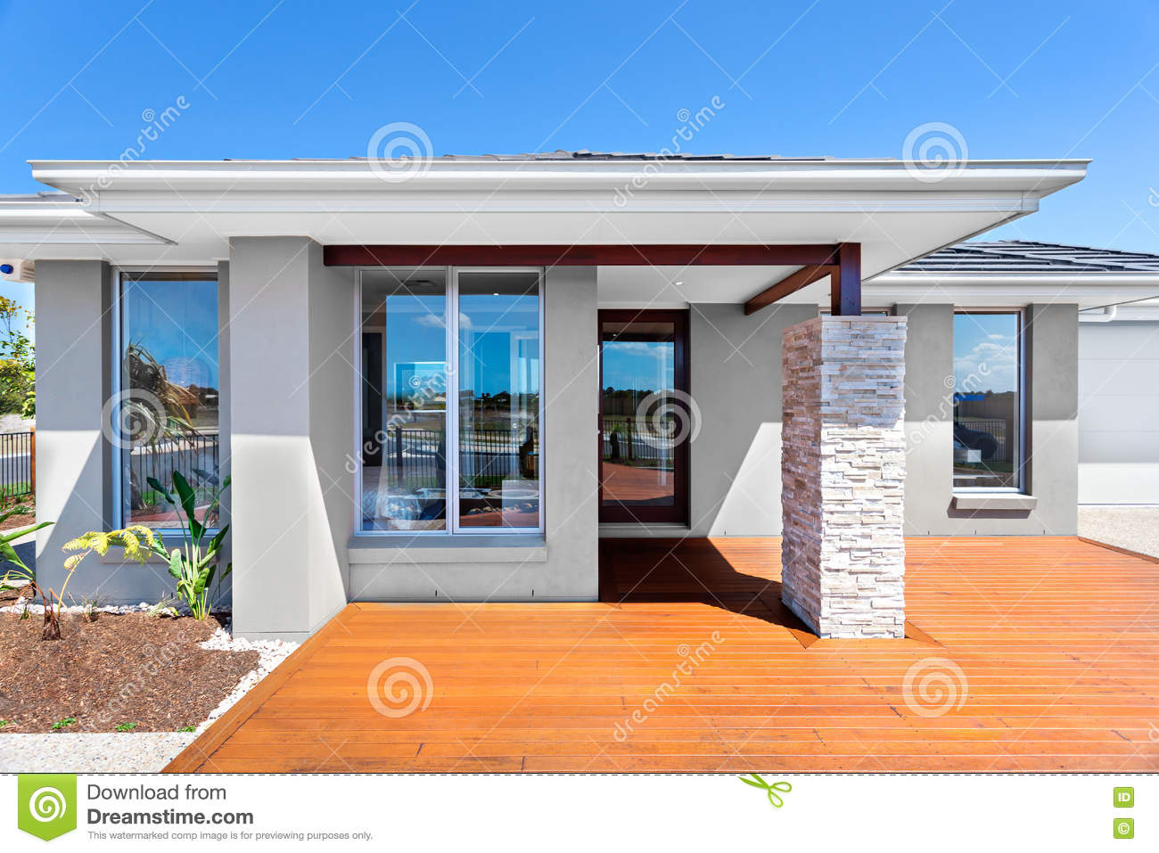 Exterior of a modern house with a wooden floor with blue sky