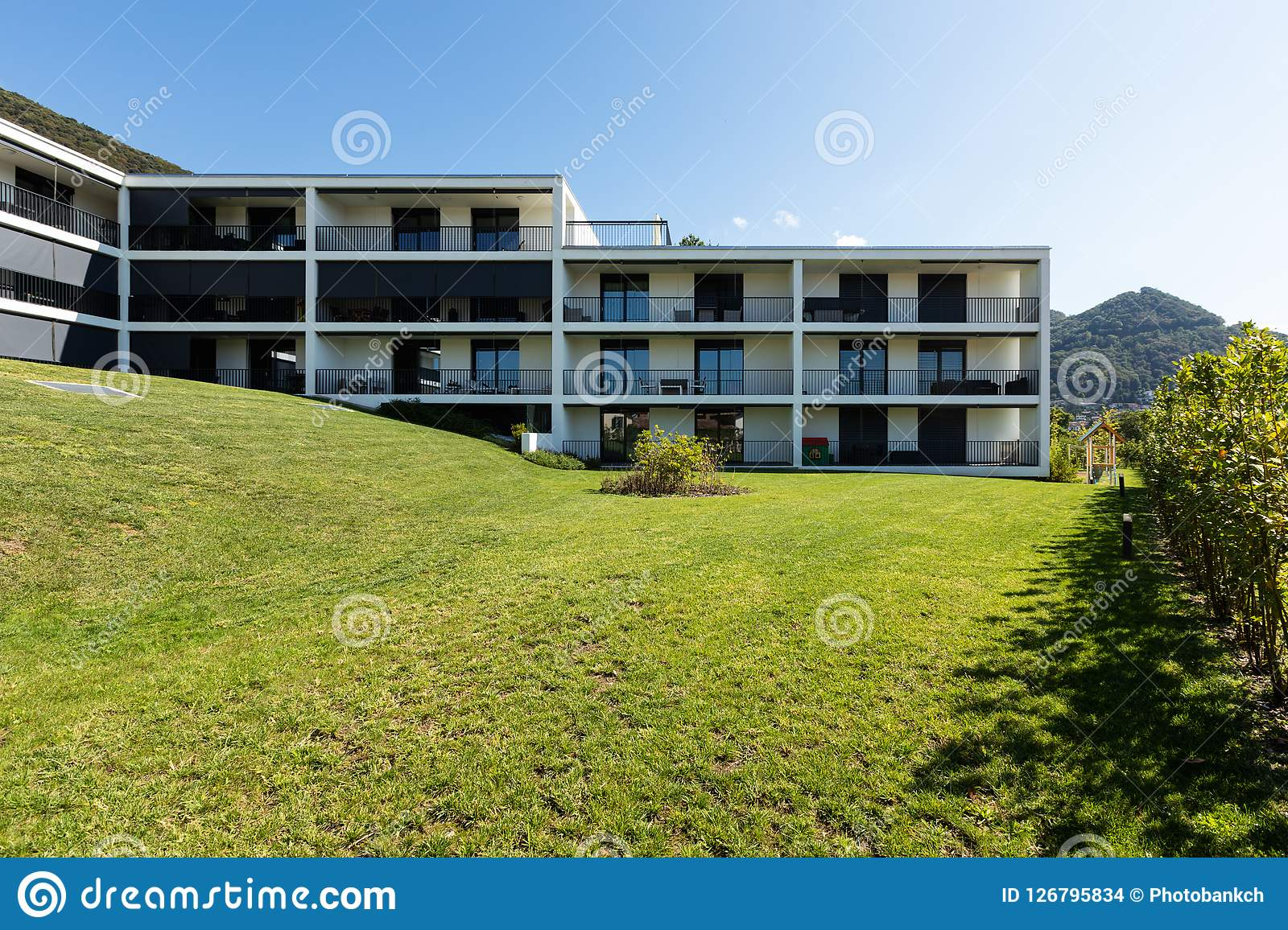 Exterior modern white condominium building with lots of lawn,