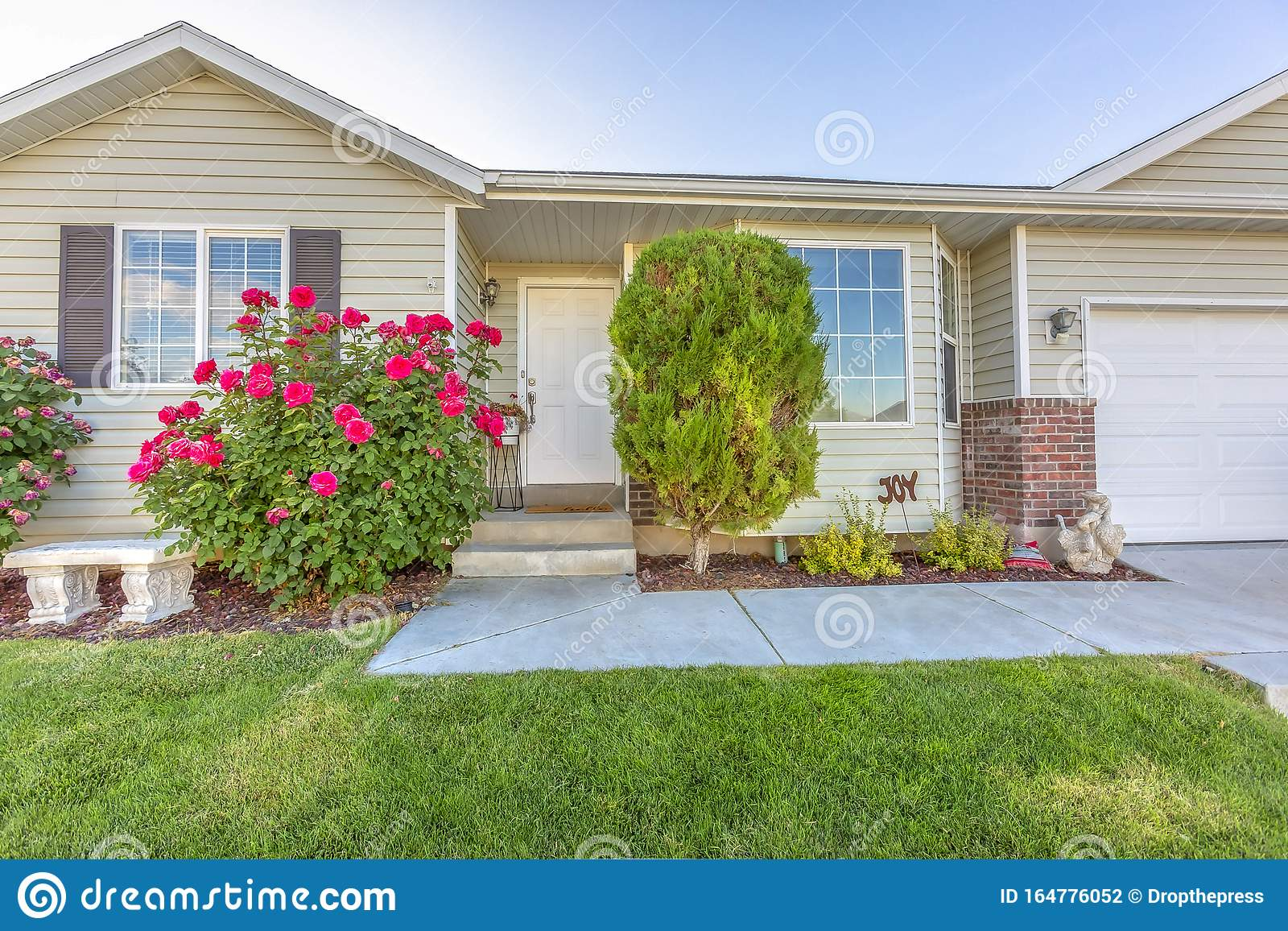 exterior one storey single family home beautiful front garden house features bay window driveway leads to 164776052