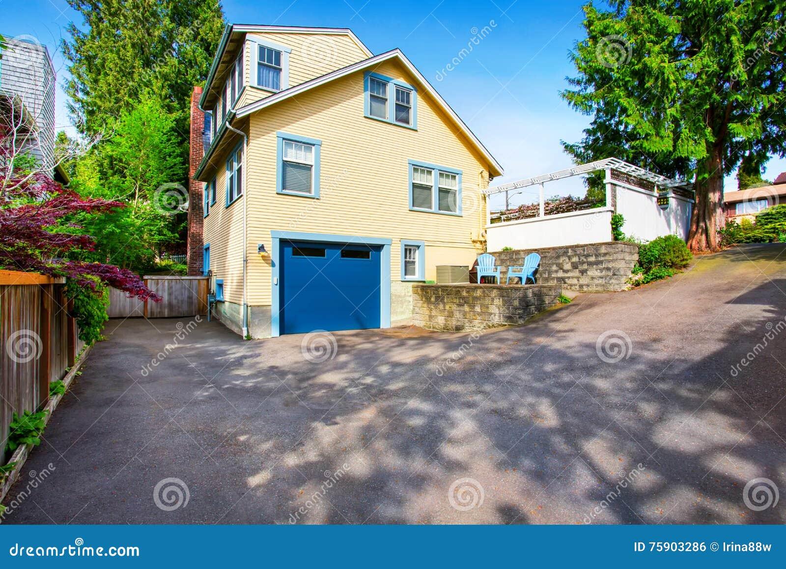 Exterior of yellow house with blue garage door and asphalt exterior of yellow house with blue garage door and asphalt driveway rubansaba