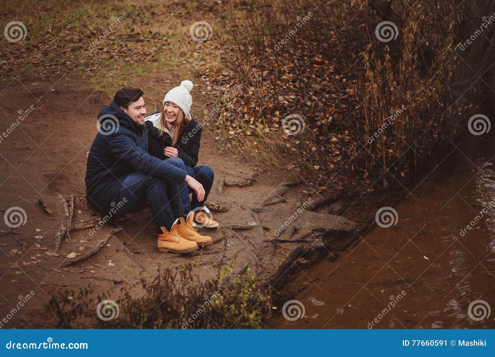 Exteriores felizes dos pares novos loving junto em acolhedor aquecem a caminhada na floresta do outono