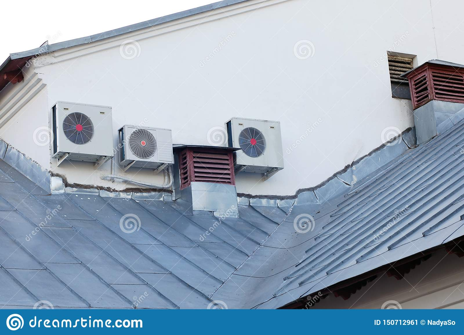 Air conditioning system and old ventilation pipes on house roof