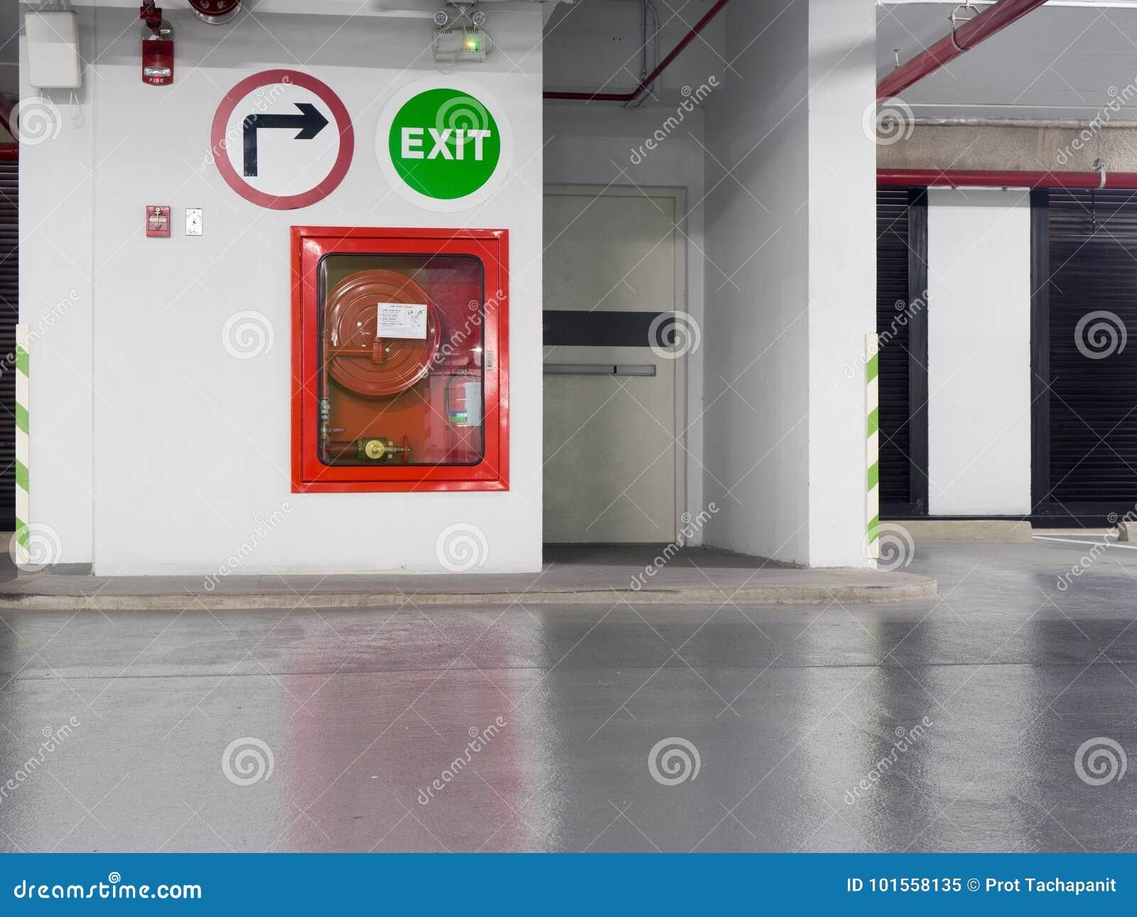 Extintor con los diversos tipos de extintores situados en la puerta de la salida de incendios en el estacionamiento