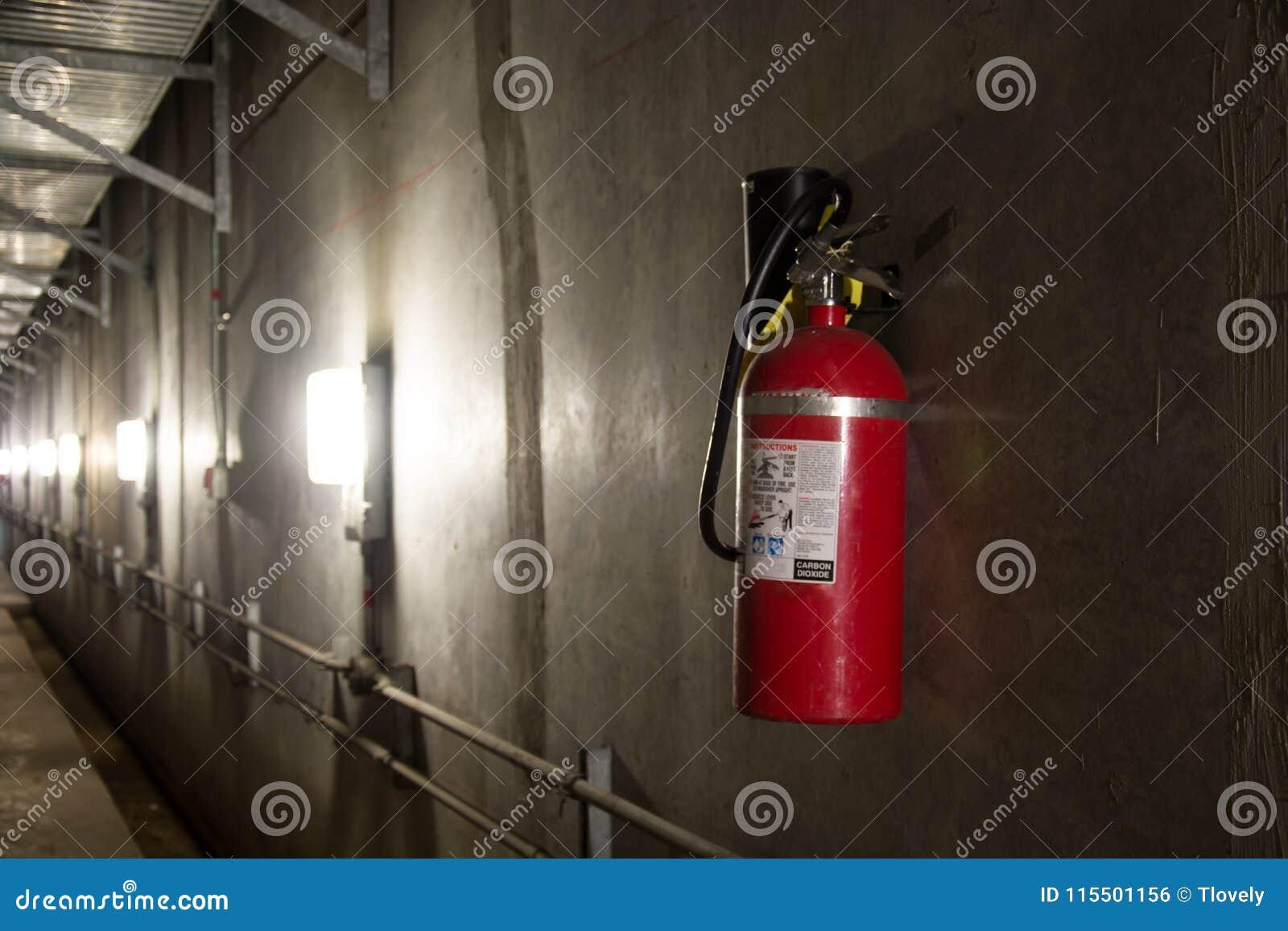 Extintor en pasillo oscuro encendido