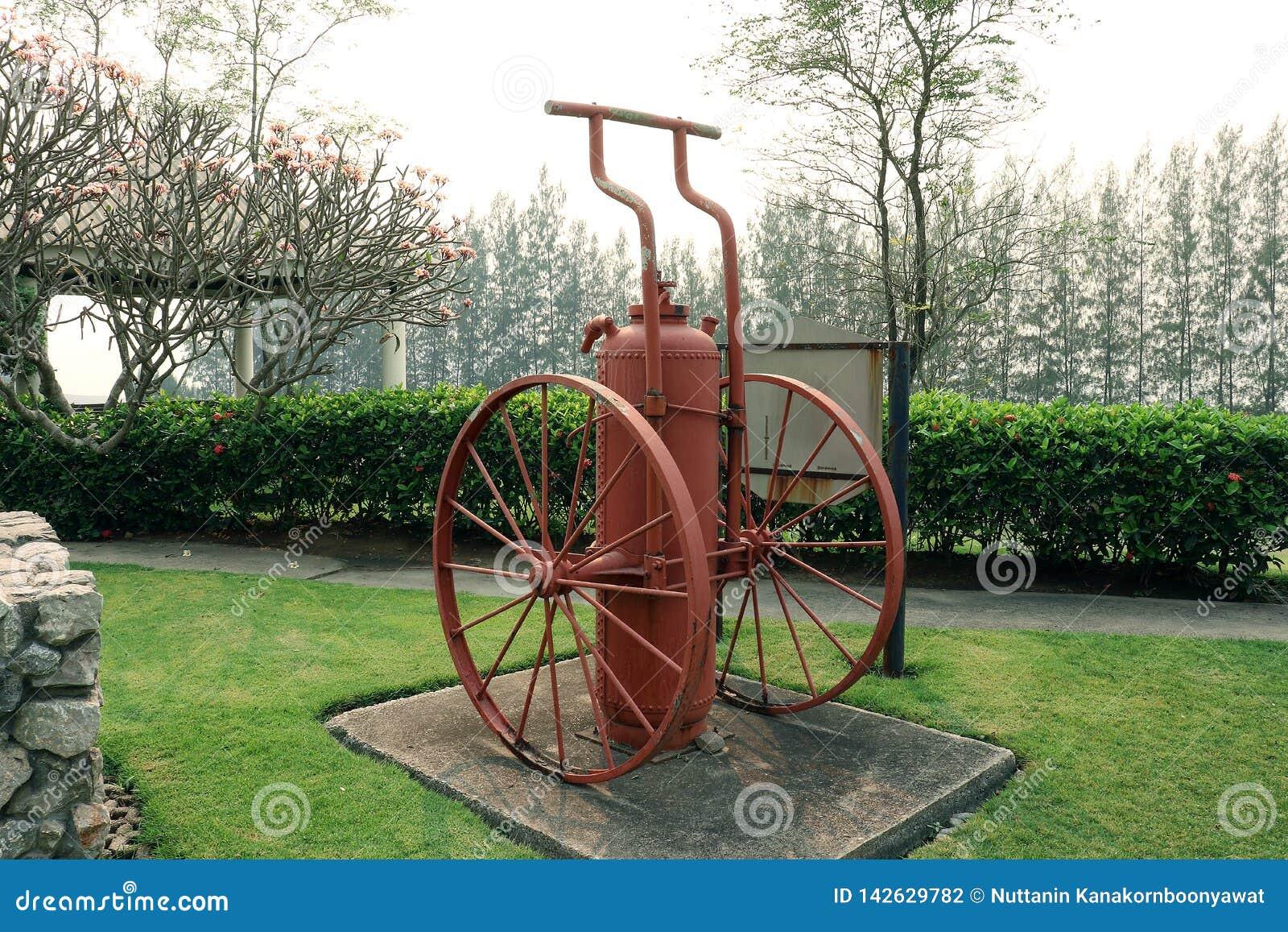 Extintor vermelho do vintage, extinguishe do fogo vermelho do ntique no jardim verde