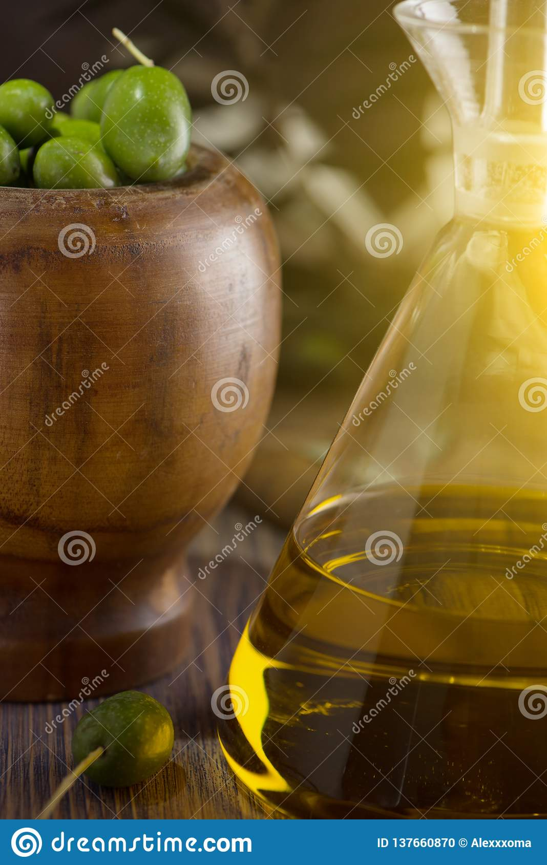 Extra jungfrulig olivolja i glasflaska med filialen av oliv på lantlig bakgrund eyes den härliga kameran för konst mode som fulla