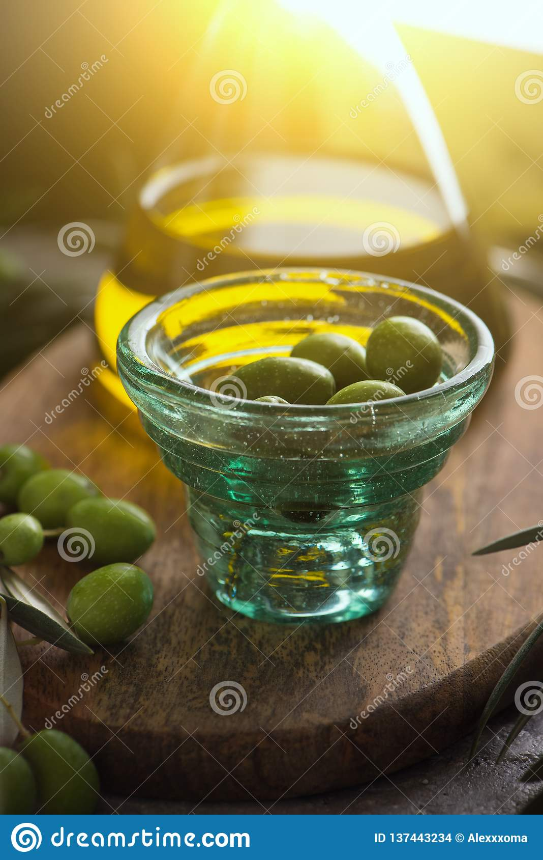 Extra jungfrulig olivolja i glasflaska med koppen av oliv på lantlig bakgrund close upp
